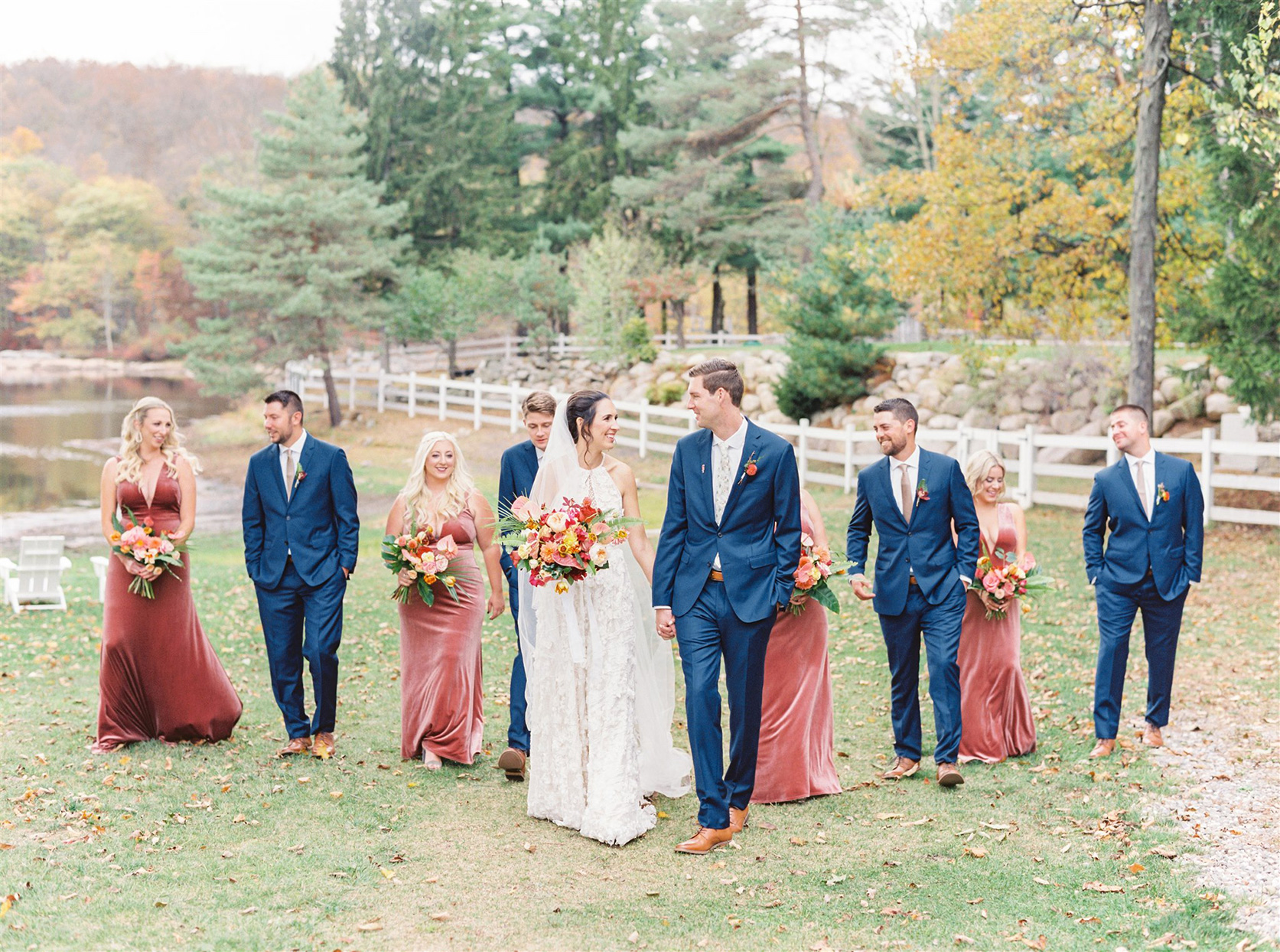 wedding party in red and blue walking with bride and groom by lake