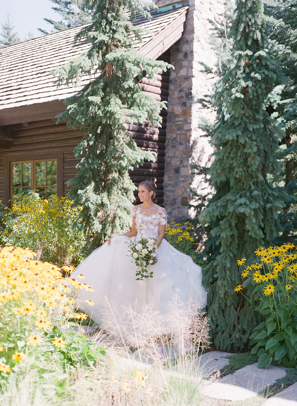 bride standing on path outside woodsy house