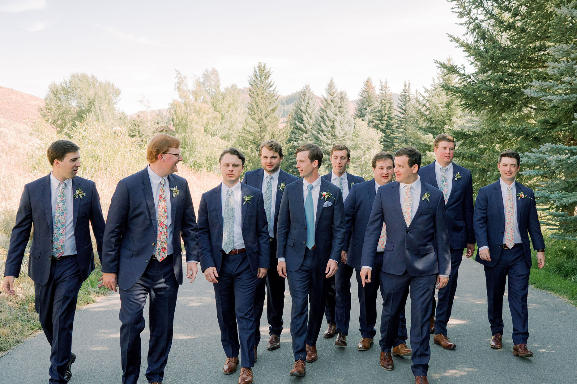 groomsmen walking down road with floral patterned ties and blue suits