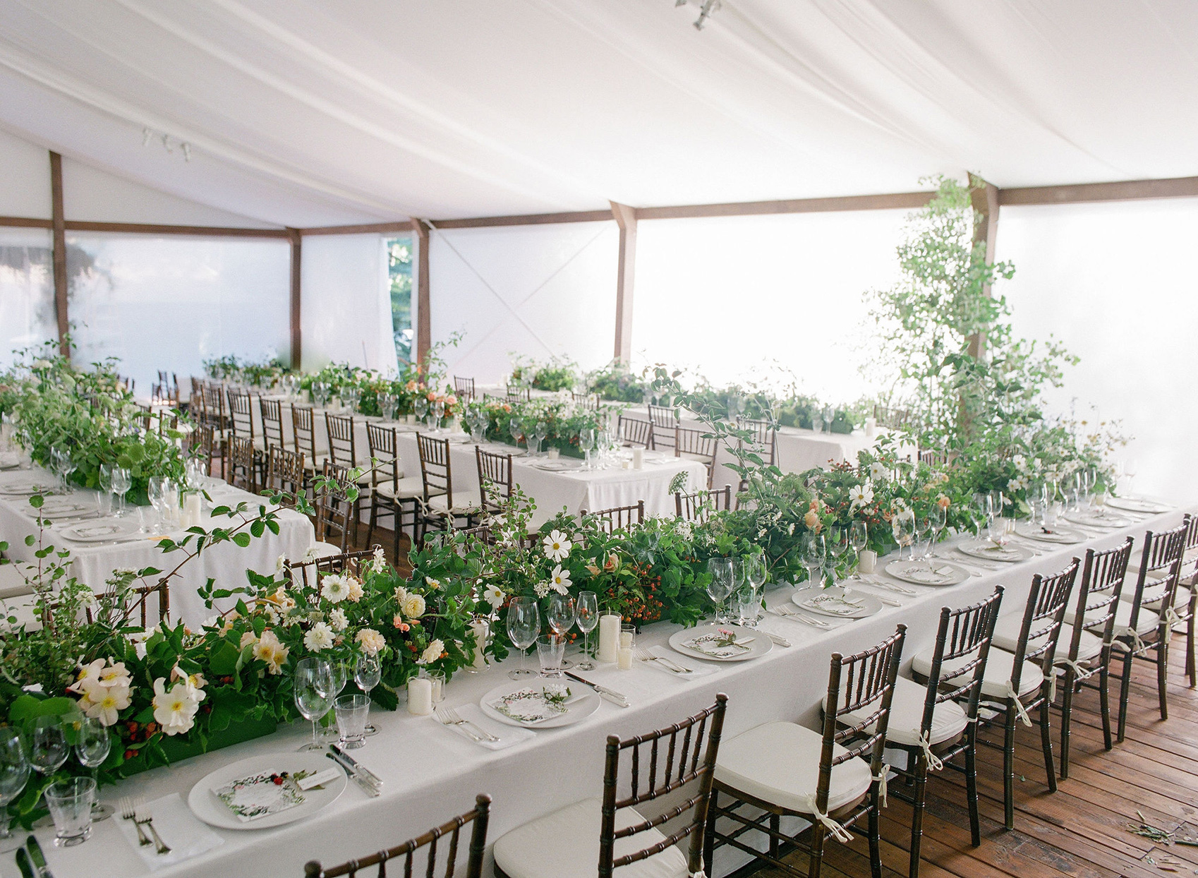 wedding reception long tables with wildflowers in tent