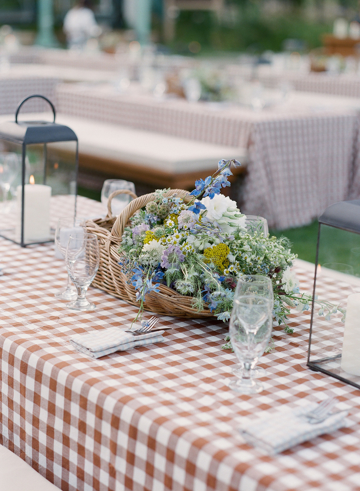 wicker basket of wildflowers centerpiece on checkered tablecloth at wedding welcome party