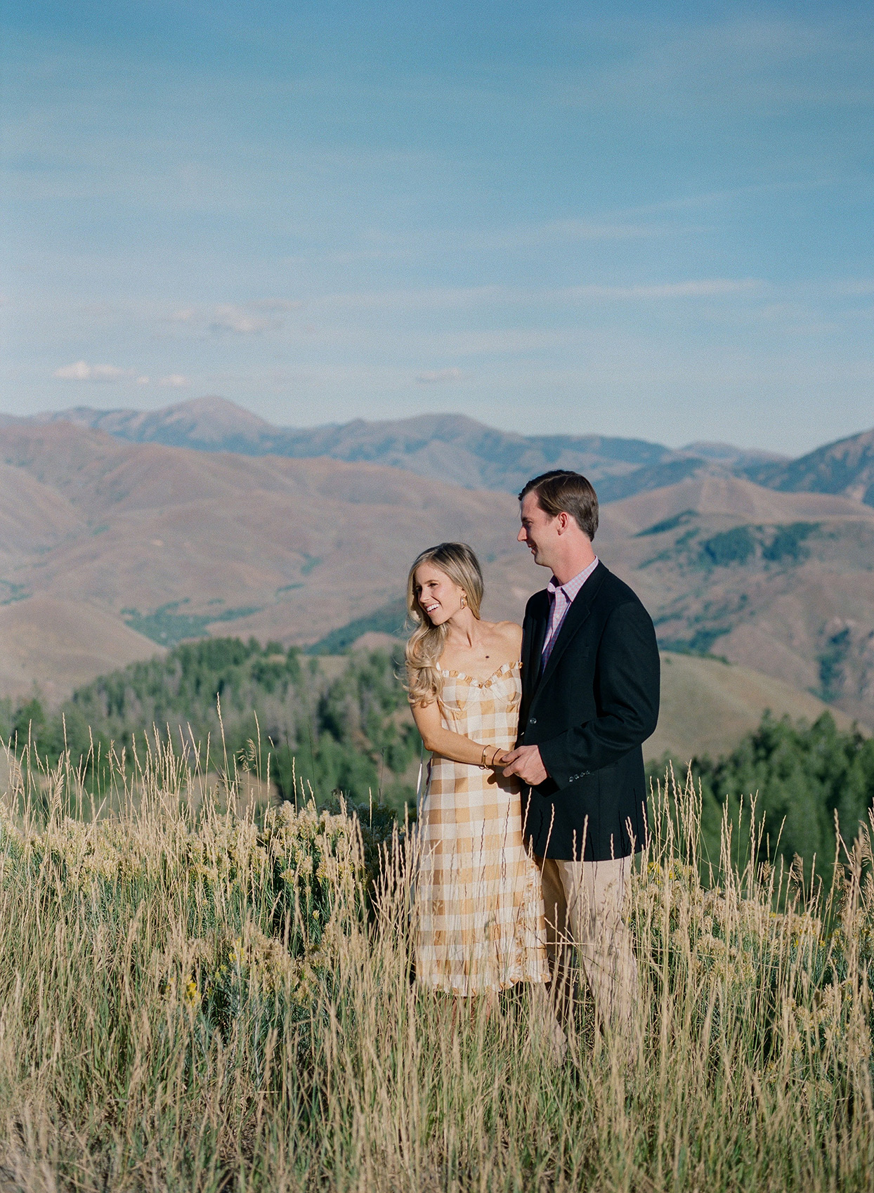 couple posing in tall grass with mountain view for wedding welcome party portraits