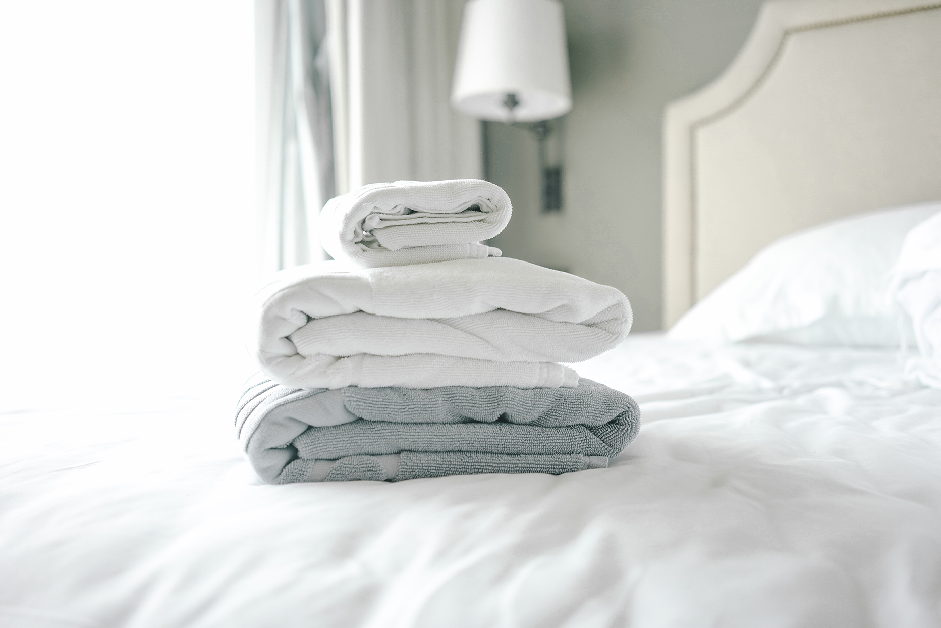 stack of light colored towels on bed