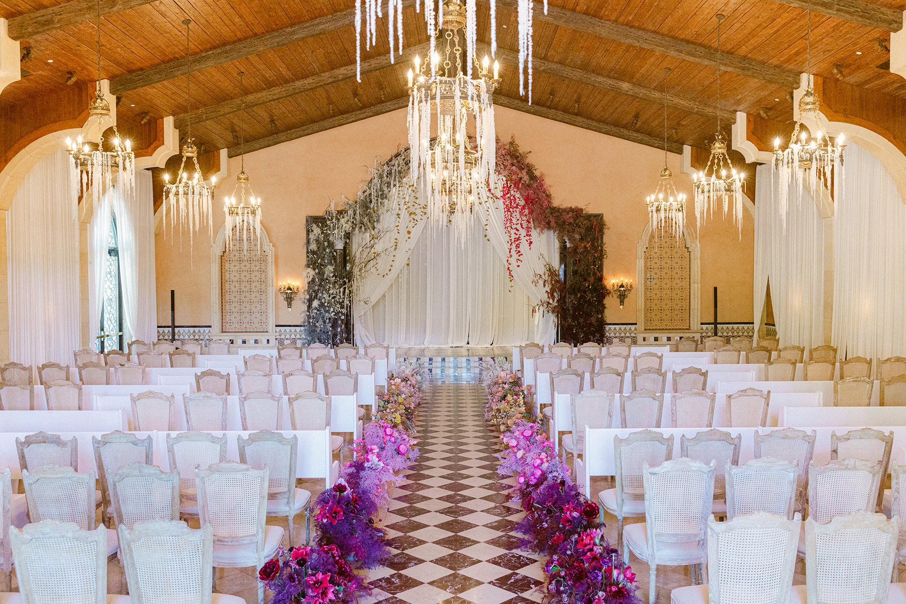 elegant wedding ceremony location with feather and flower bouquets lining the aisle