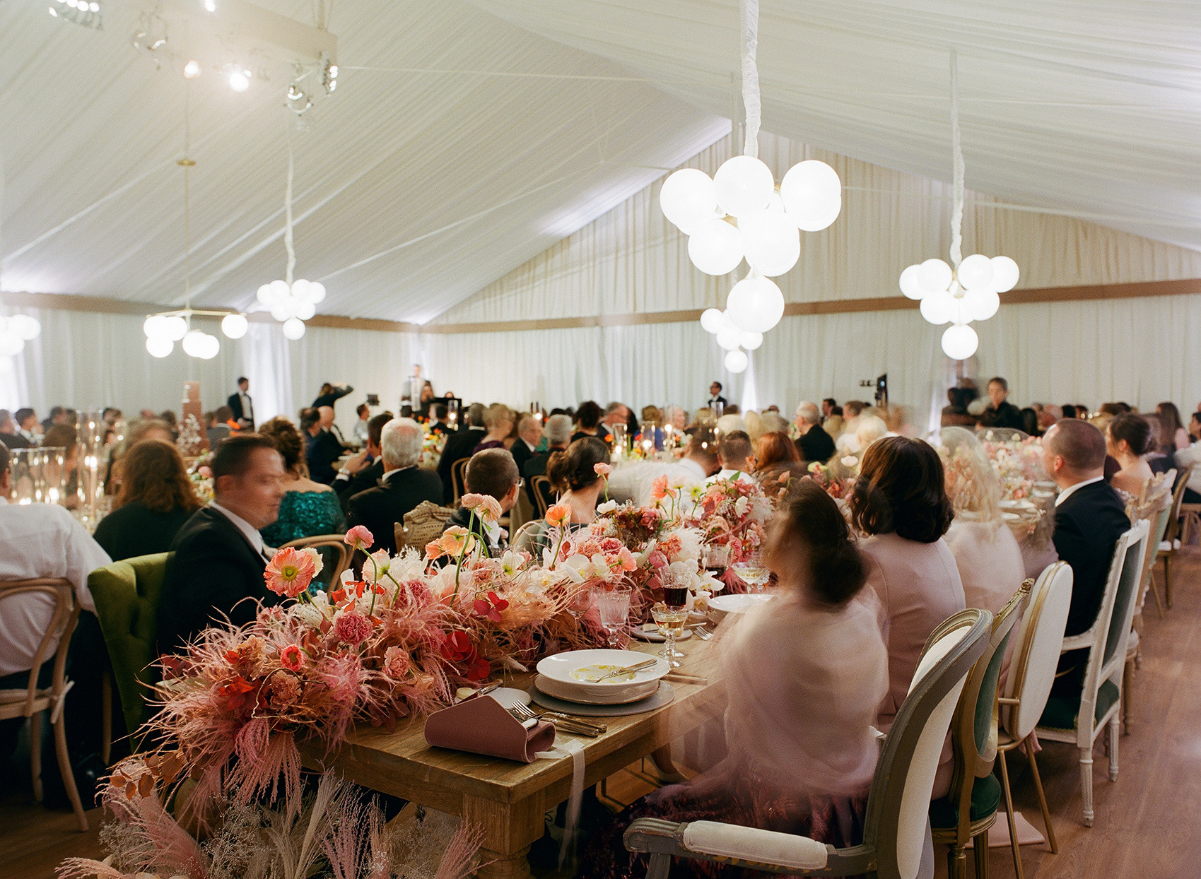 guests sitting at wooden tables with floral and feather garland centerpieces