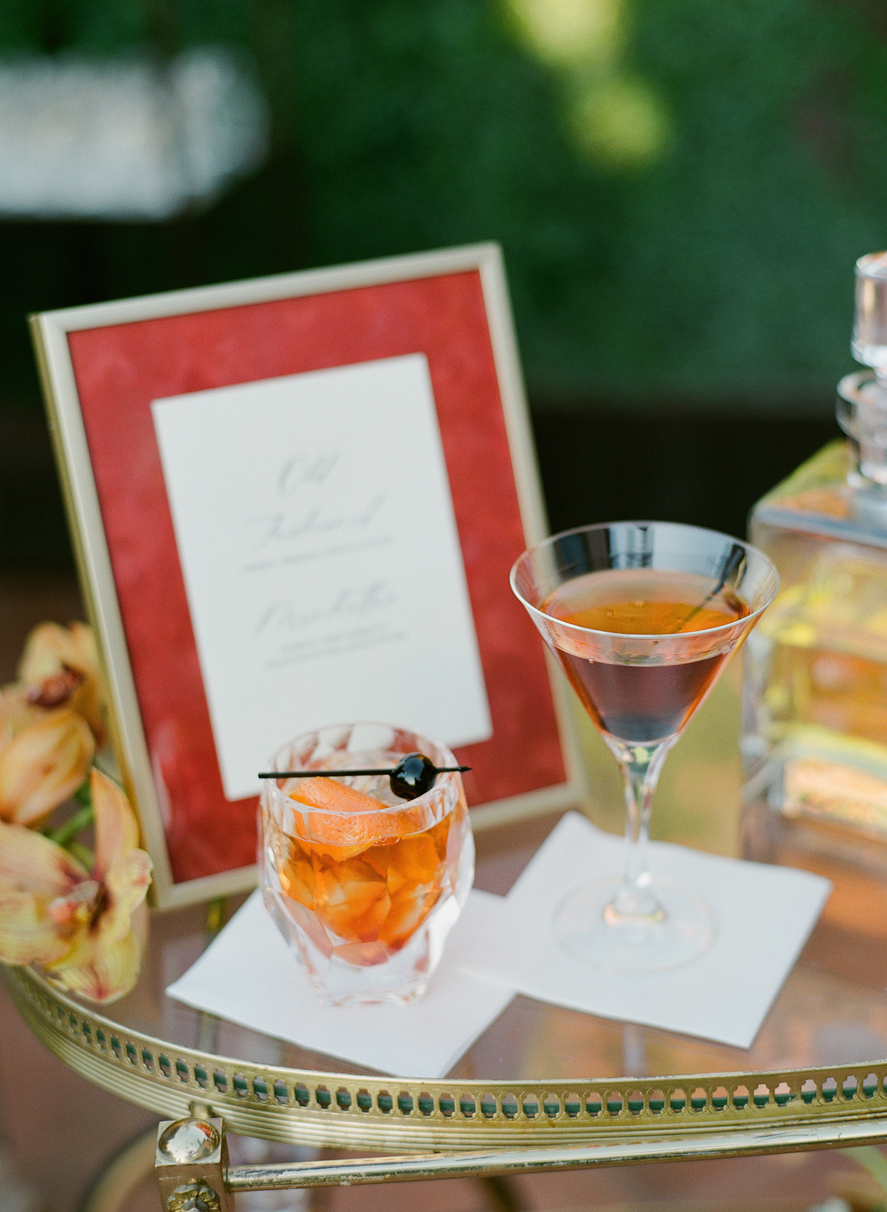 glass table with wedding signature cocktails and sign