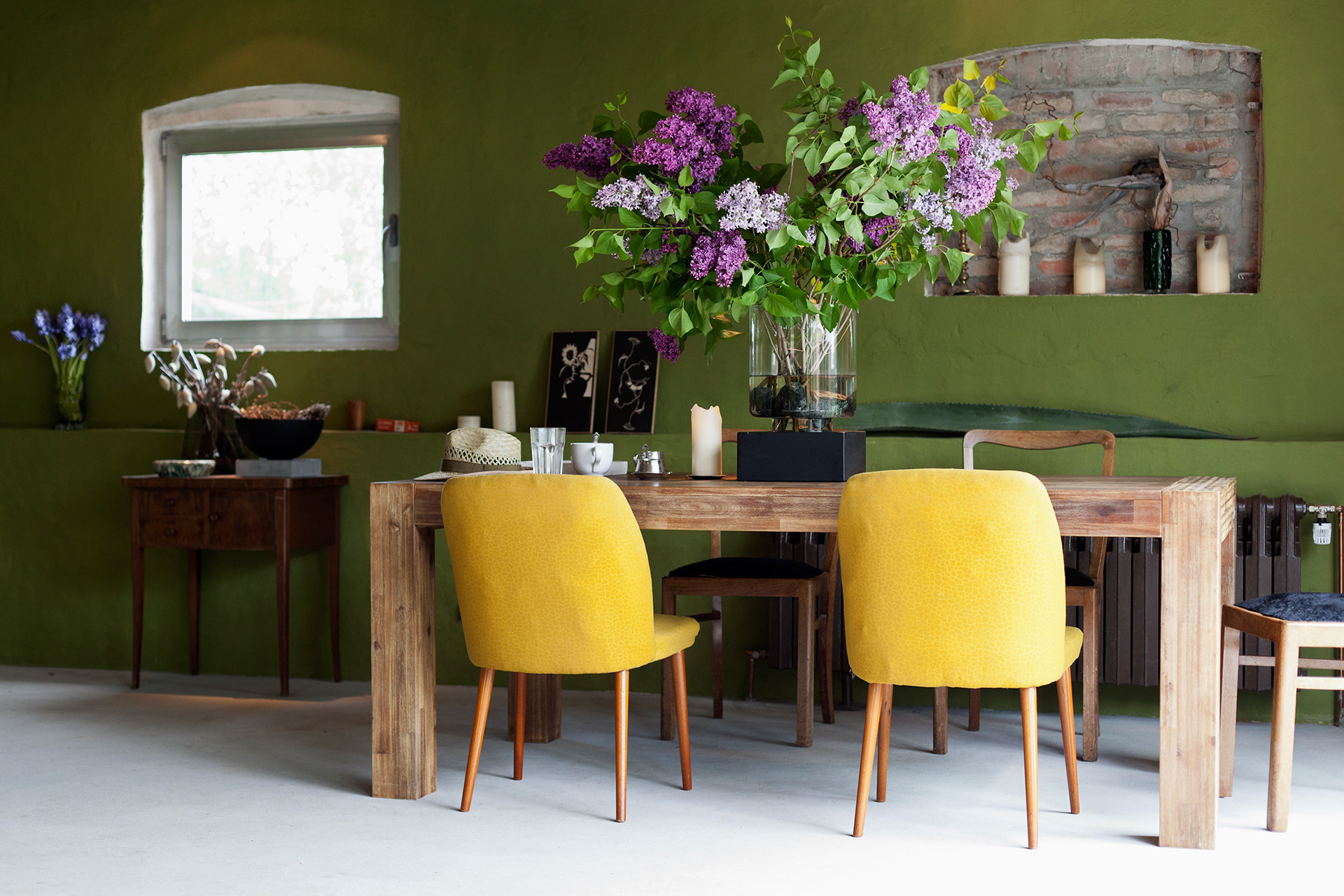 A stylish colorful dining room with yellow chairs and lilacs
