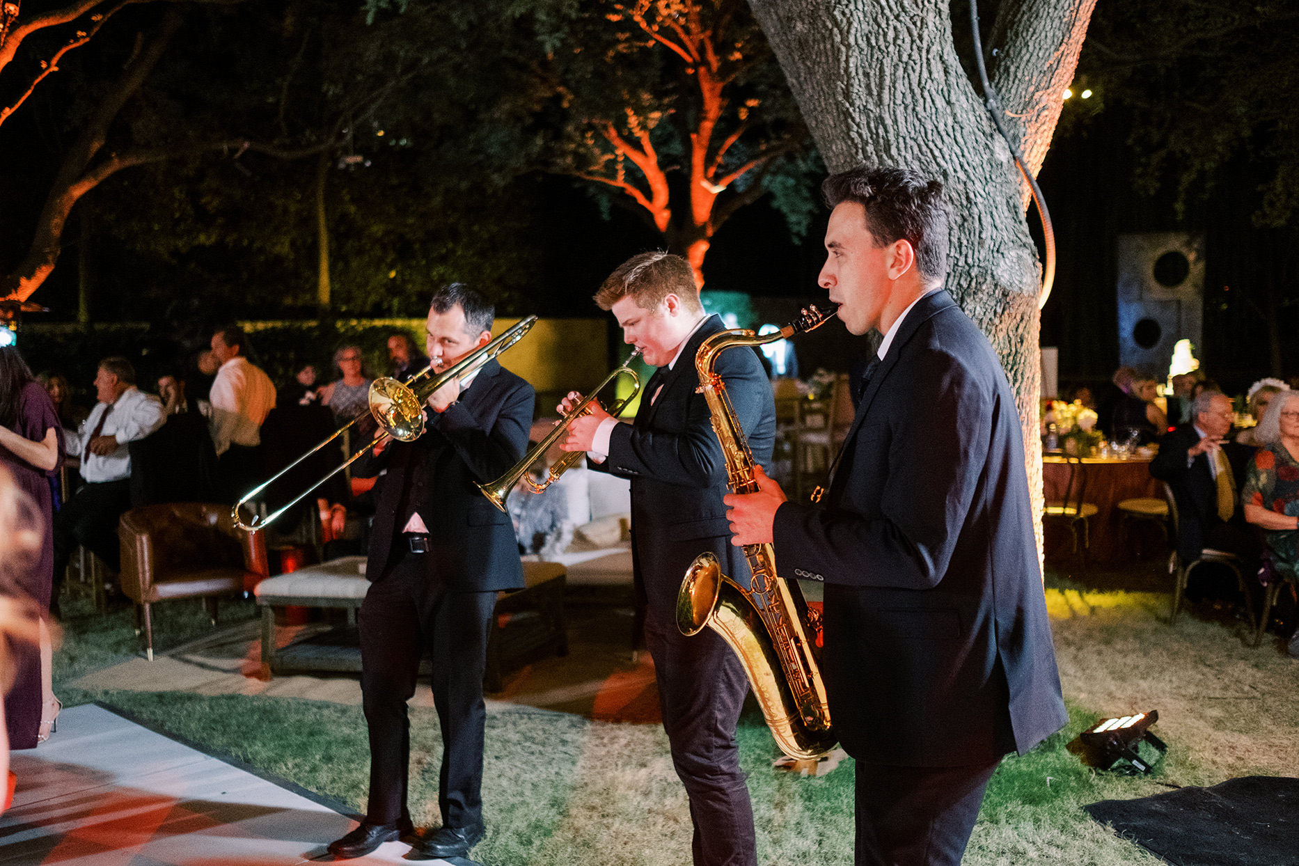 wedding band playing brass instruments outdoors at reception