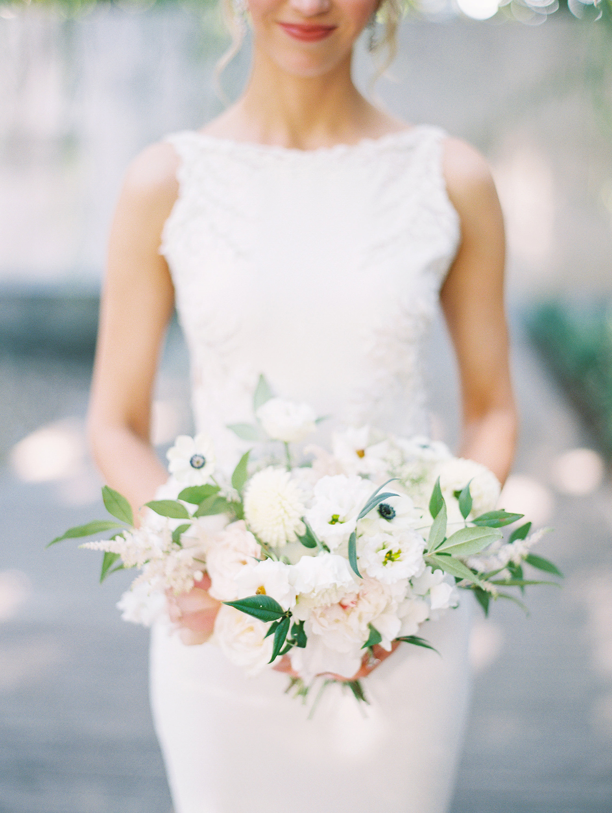 bride holding simple white floral bouquet