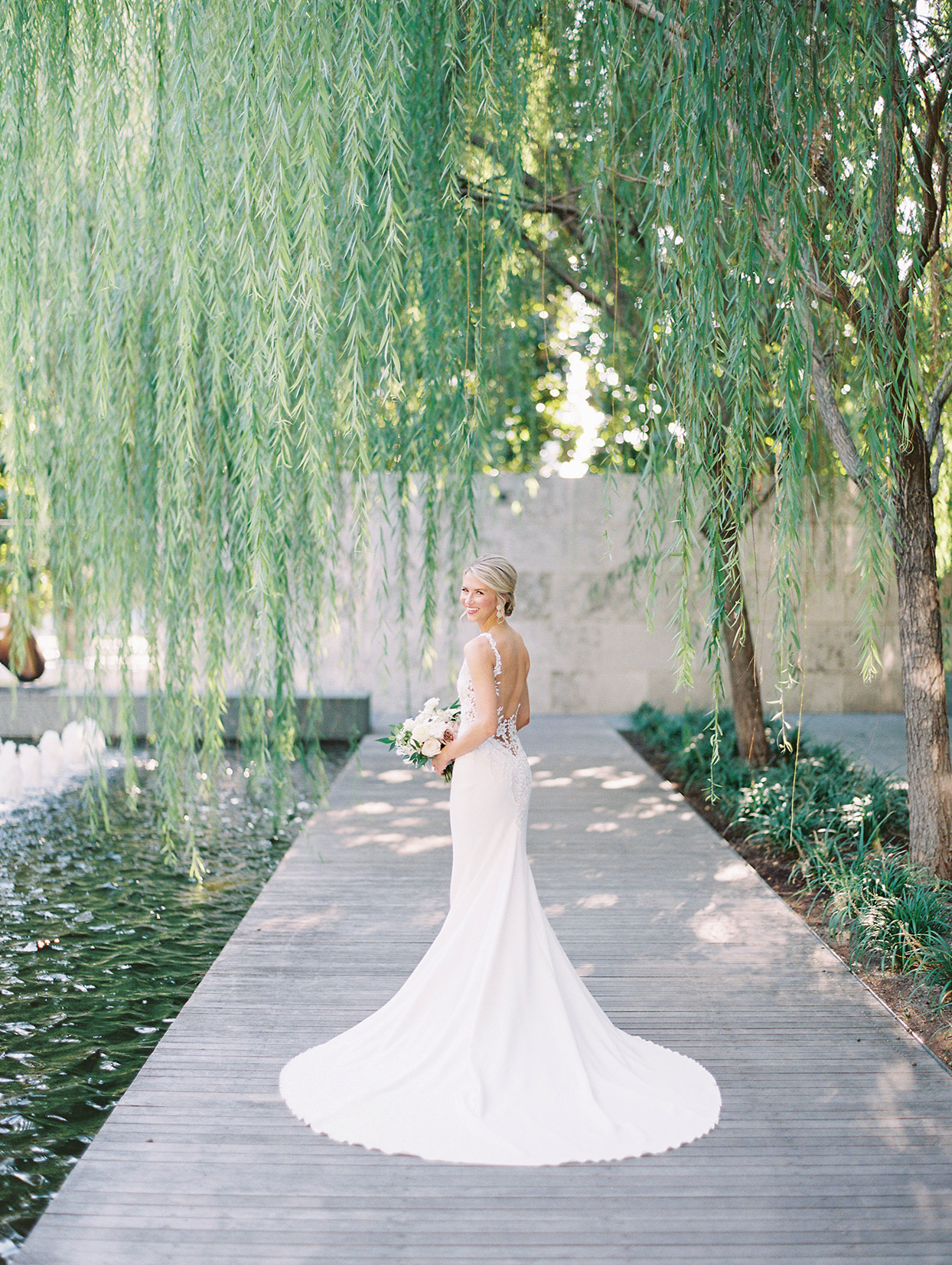 bride standing on boardwalk under willow tree