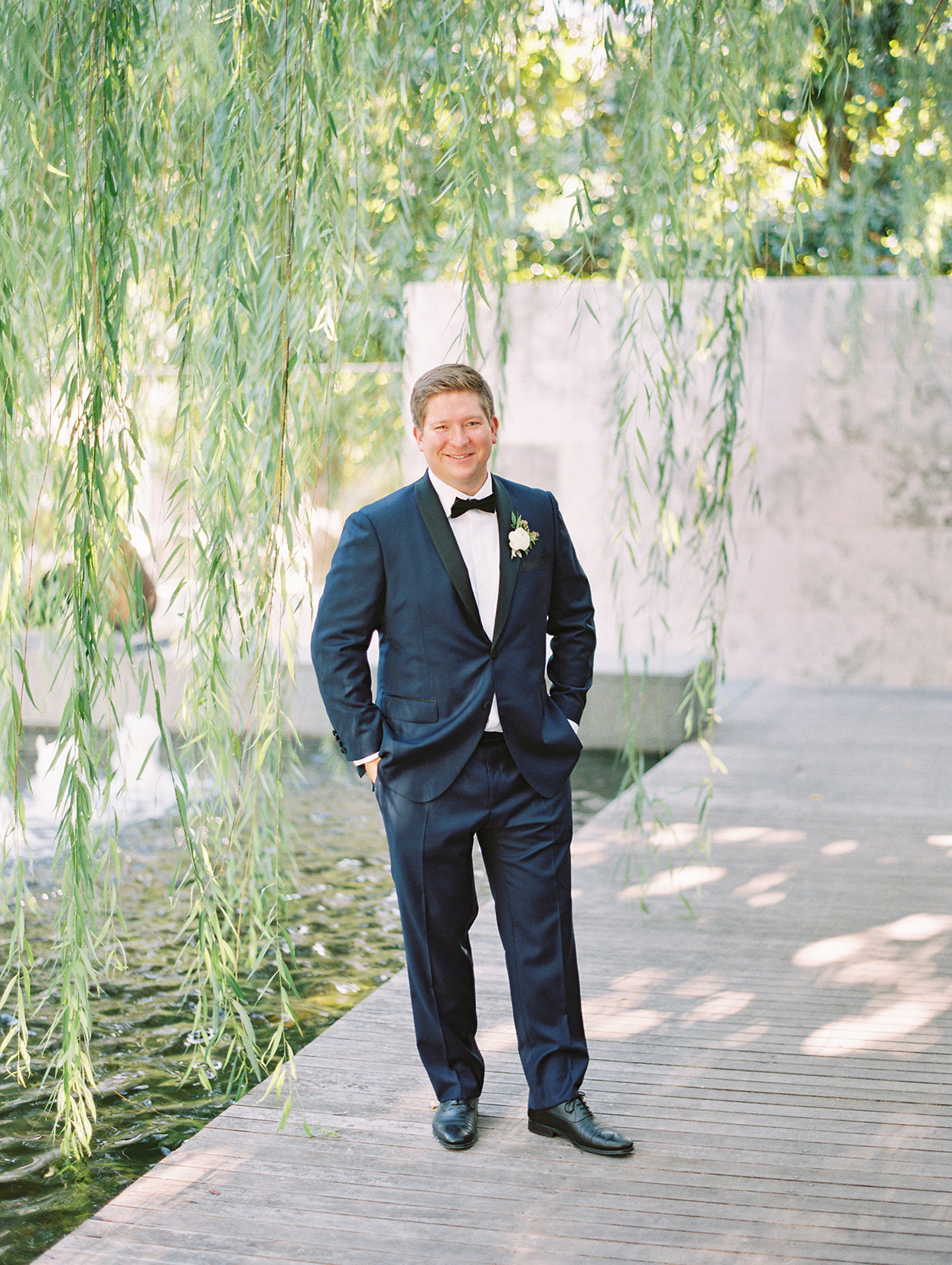 groom in blue suit on boardwalk under willow tree