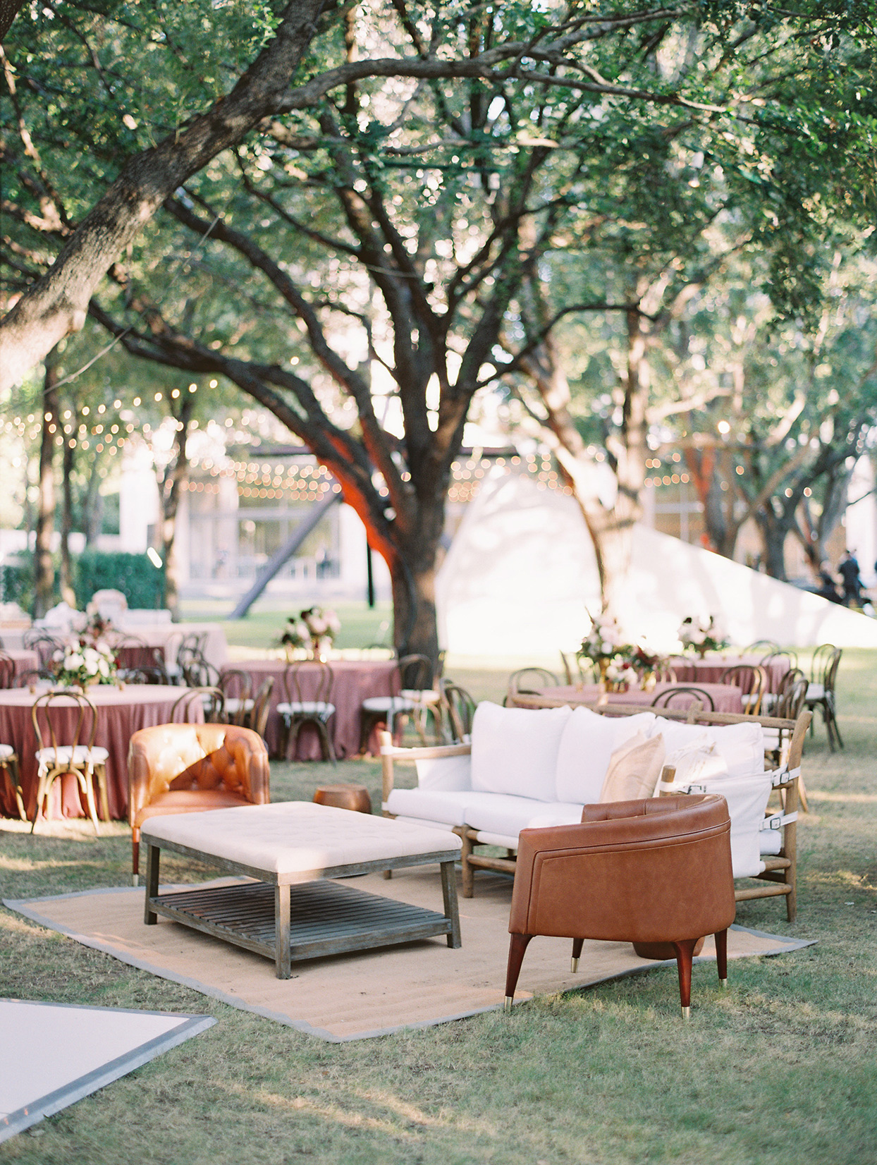 wedding outdoor lounging area with white couches and leather chairs