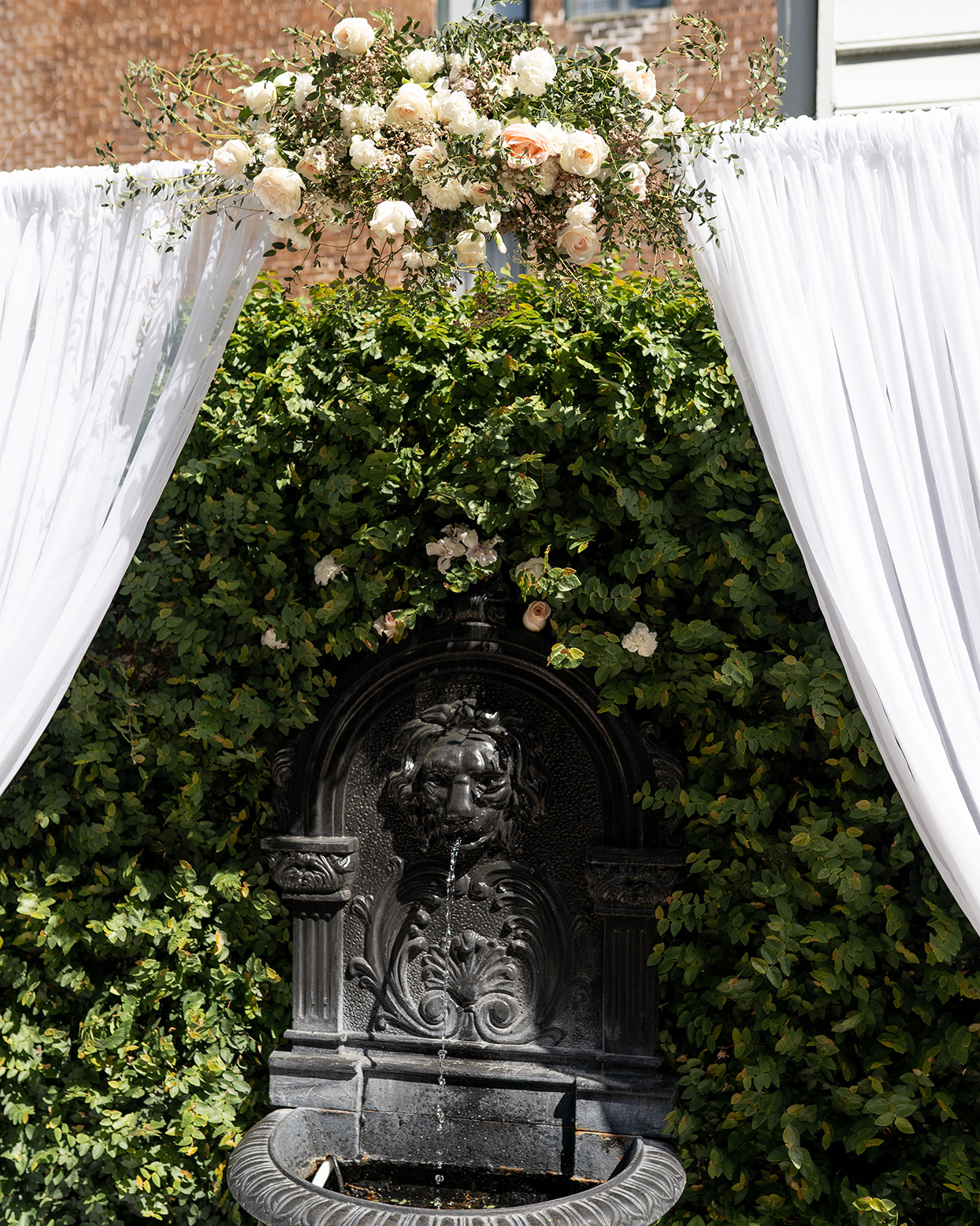 wedding ceremony location in front of fountain with floral and drapery arch