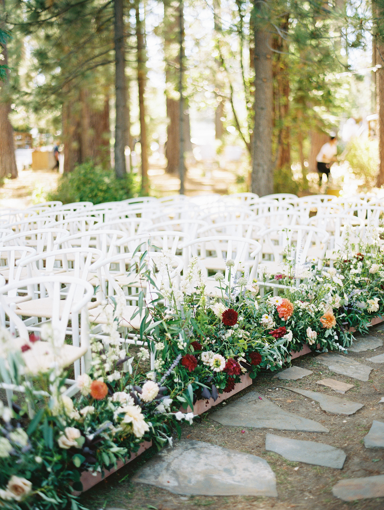white chairs set up for wedding ceremony with wildflowers lining the aisle