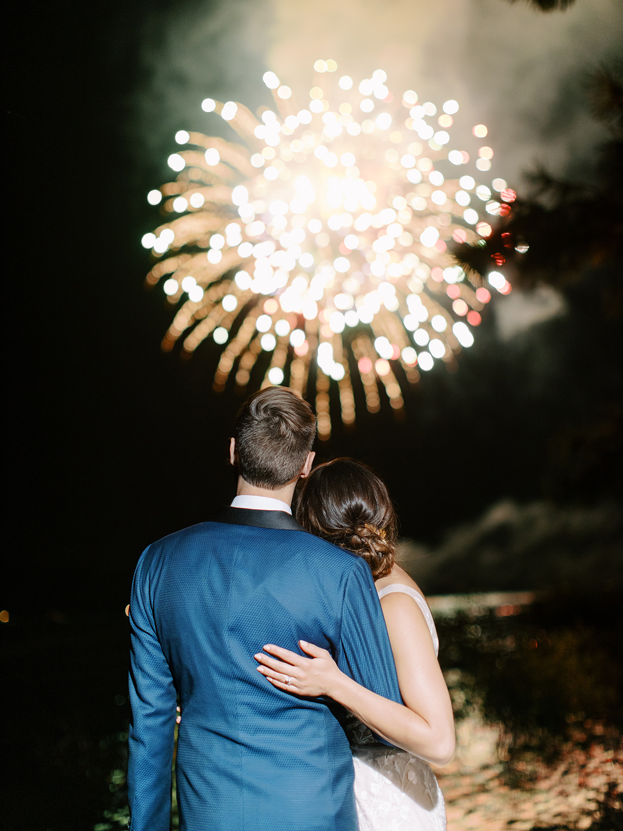 bride and groom watching fireworks after reception
