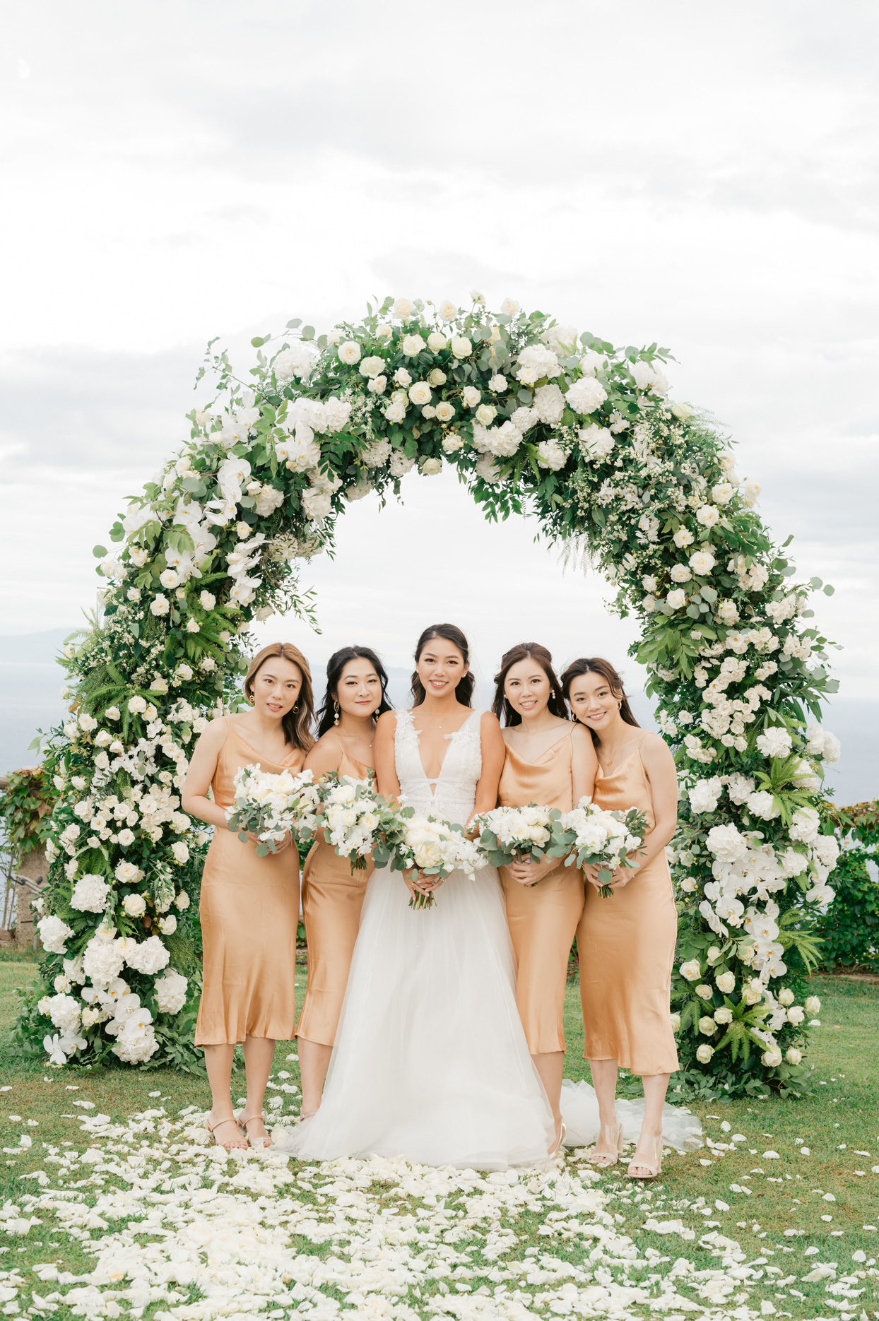 bride with bridesmaids wearing tea length orange dresses under floral wedding arch