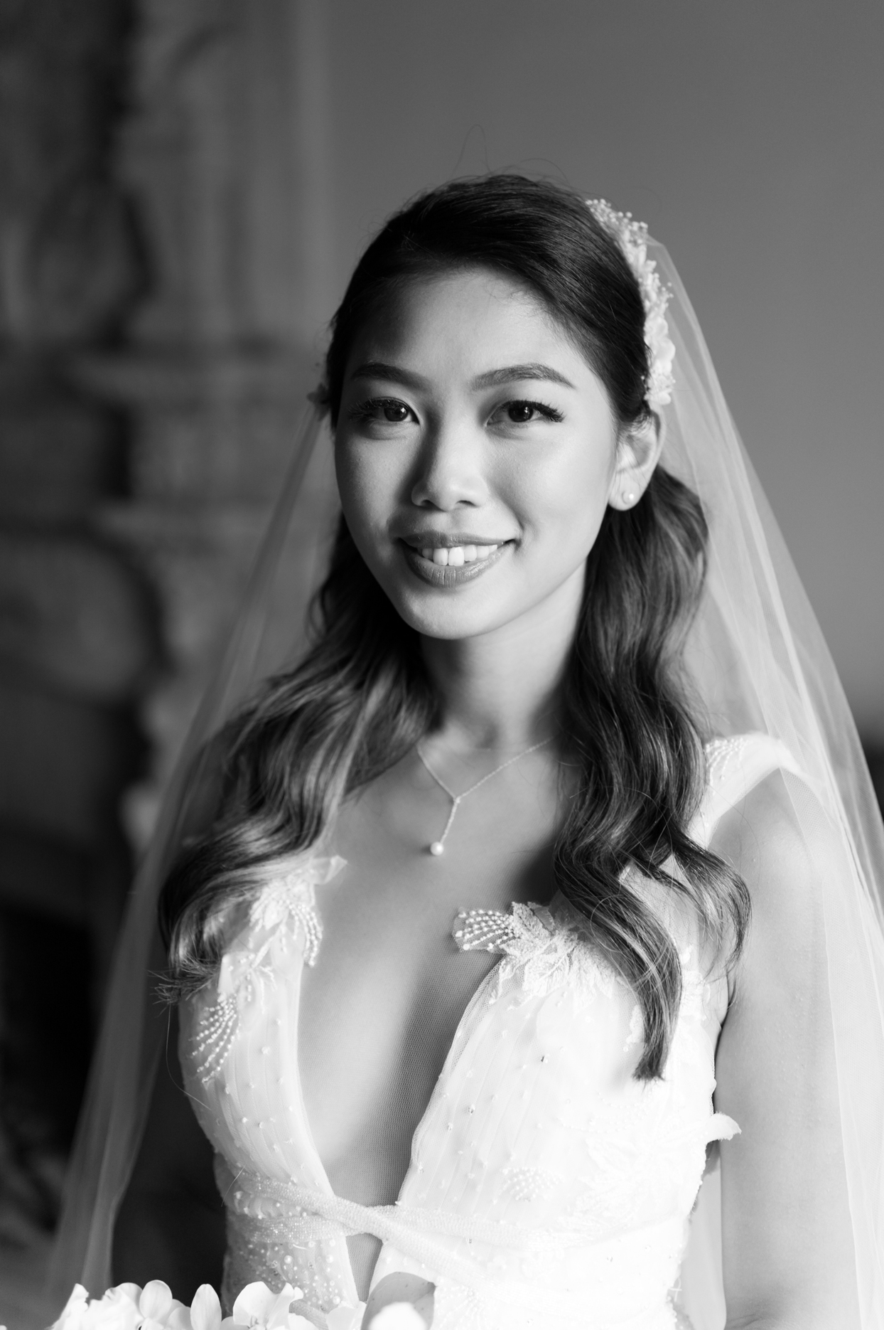 bride smiling for portrait wearing wedding dress with veil and minimal pearl necklace
