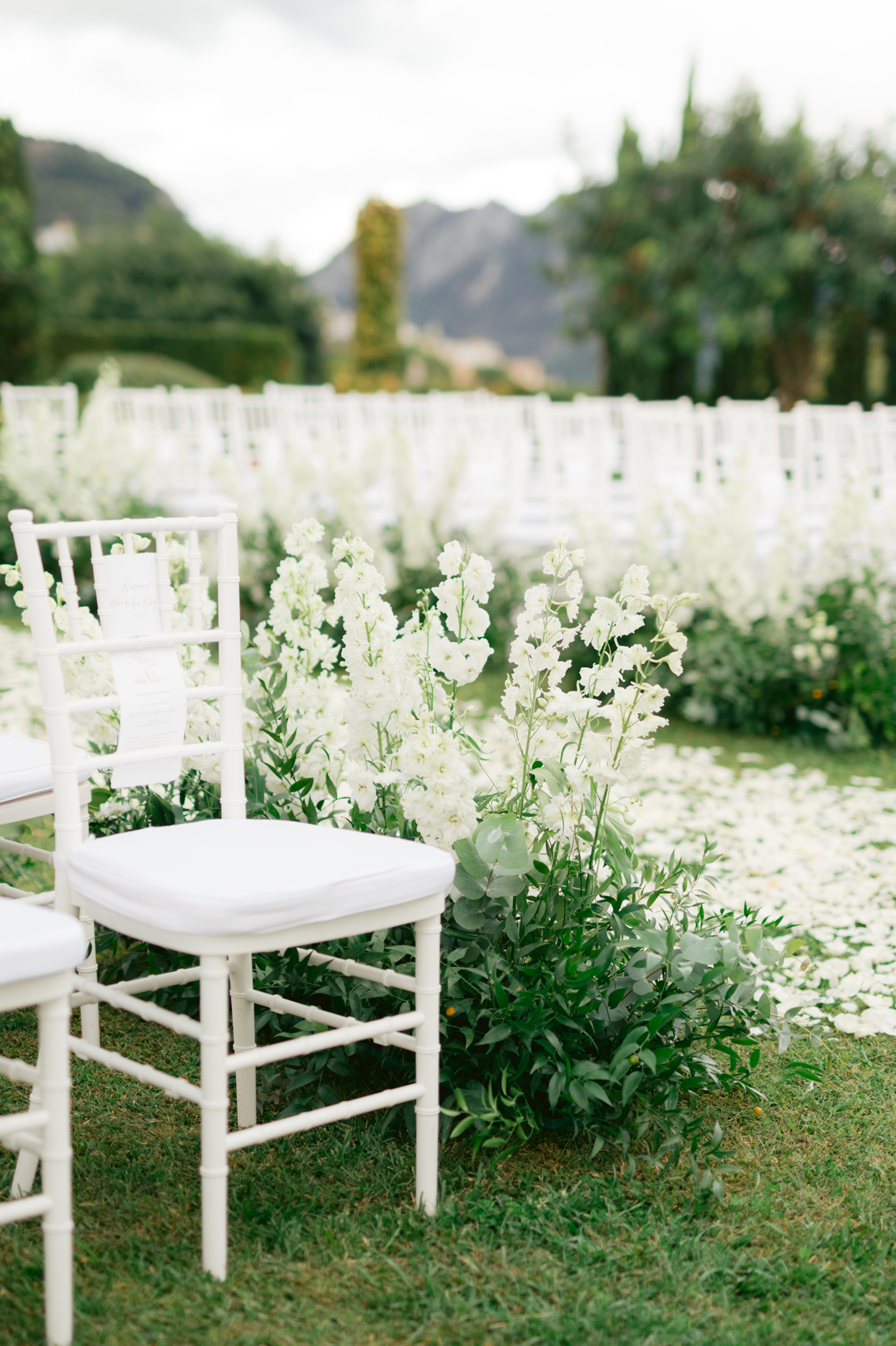 white floral lined wedding aisle with white seating