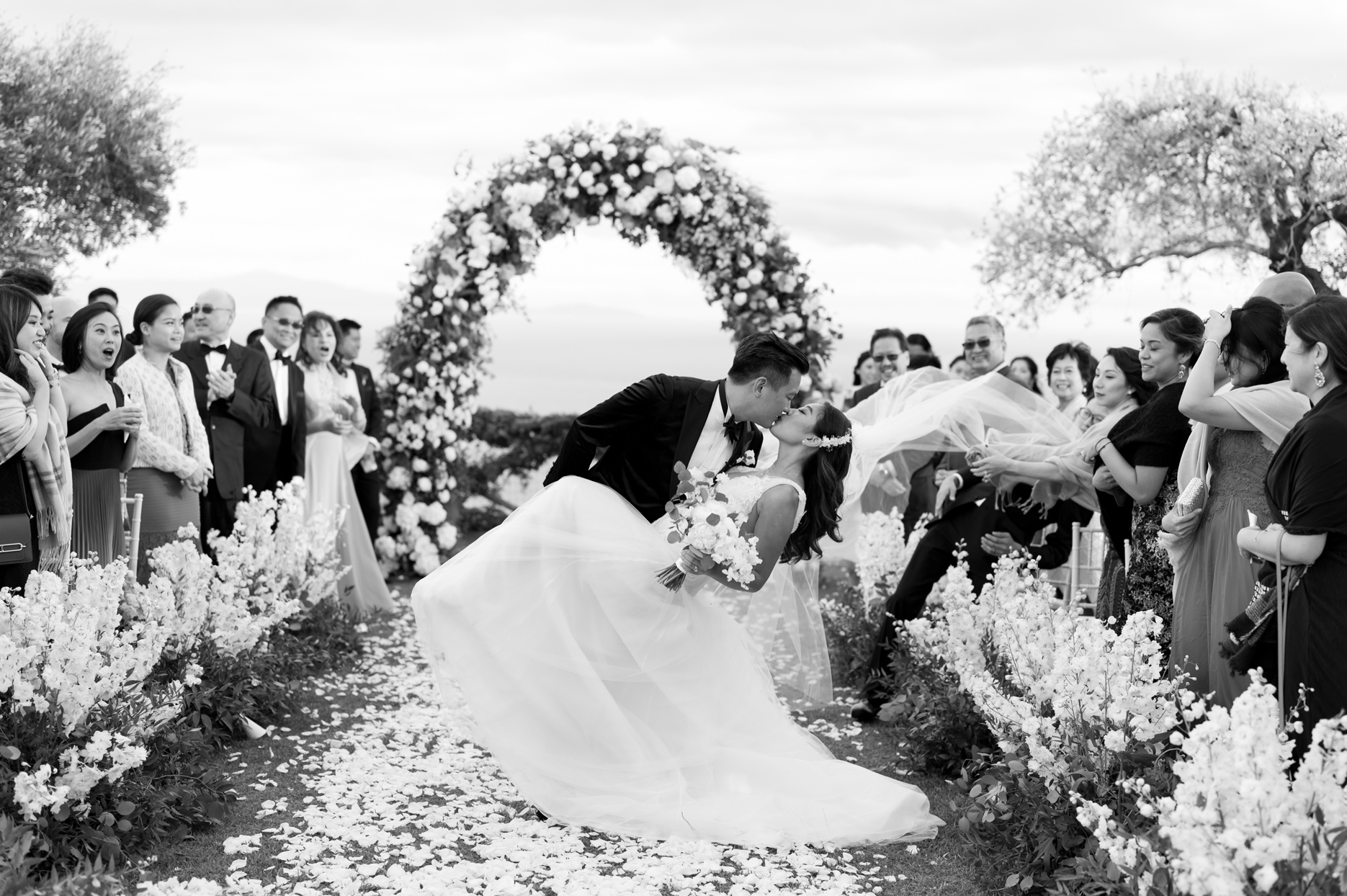 groom dips bride during recessional surrounded by guests