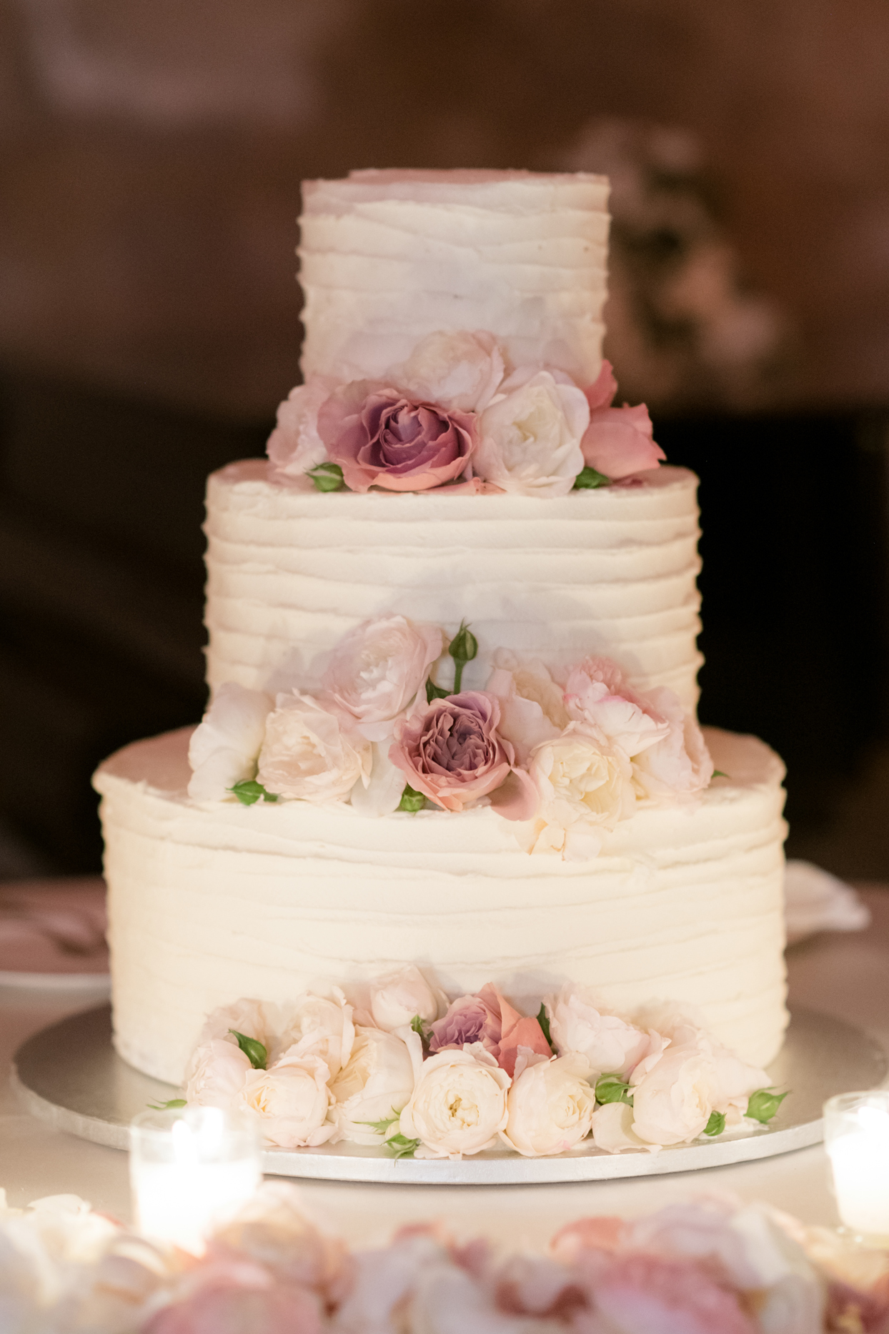 three layer white frosted pink and white floral accent wedding cake