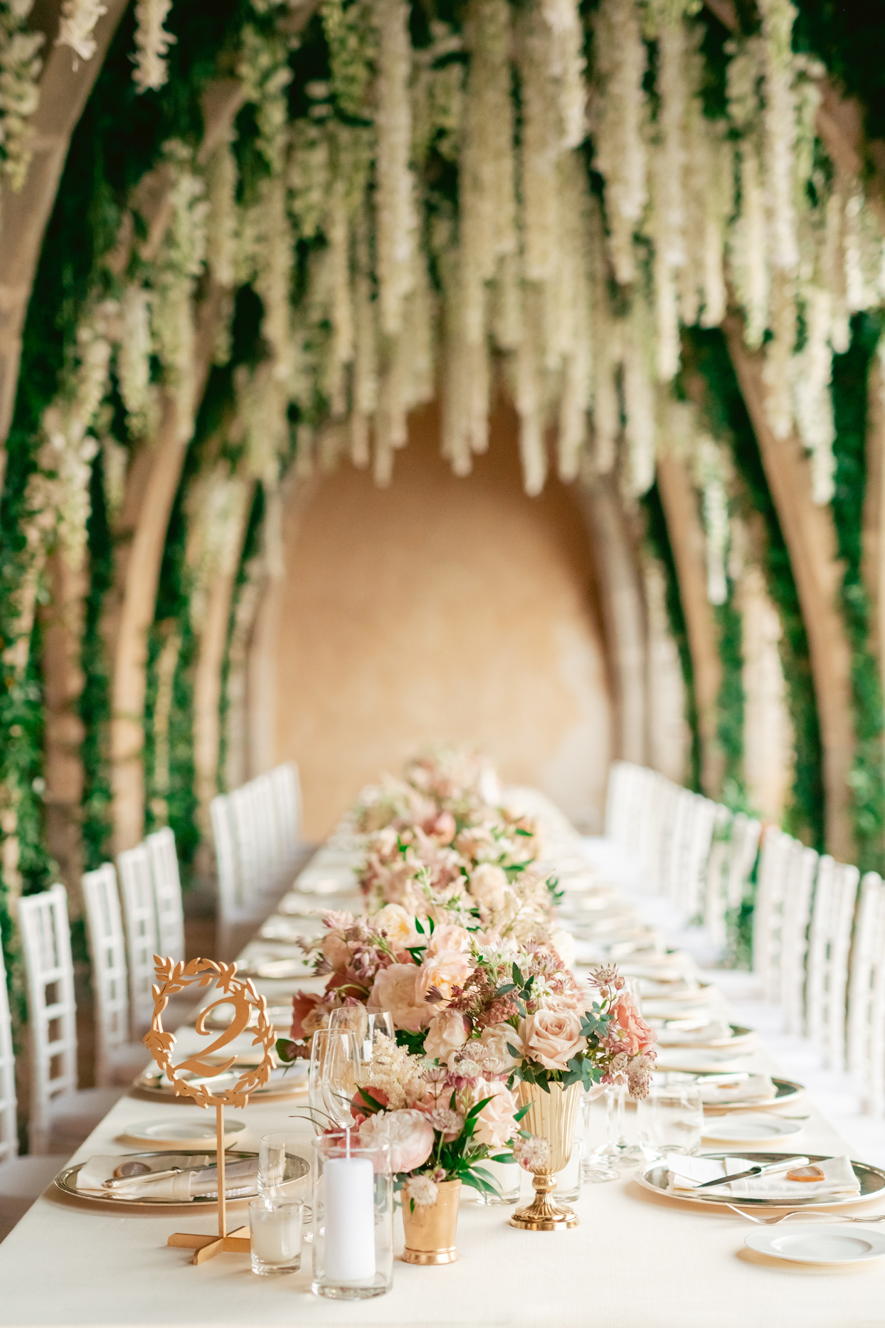 long white linen covered reception tables under hanging white floral decor