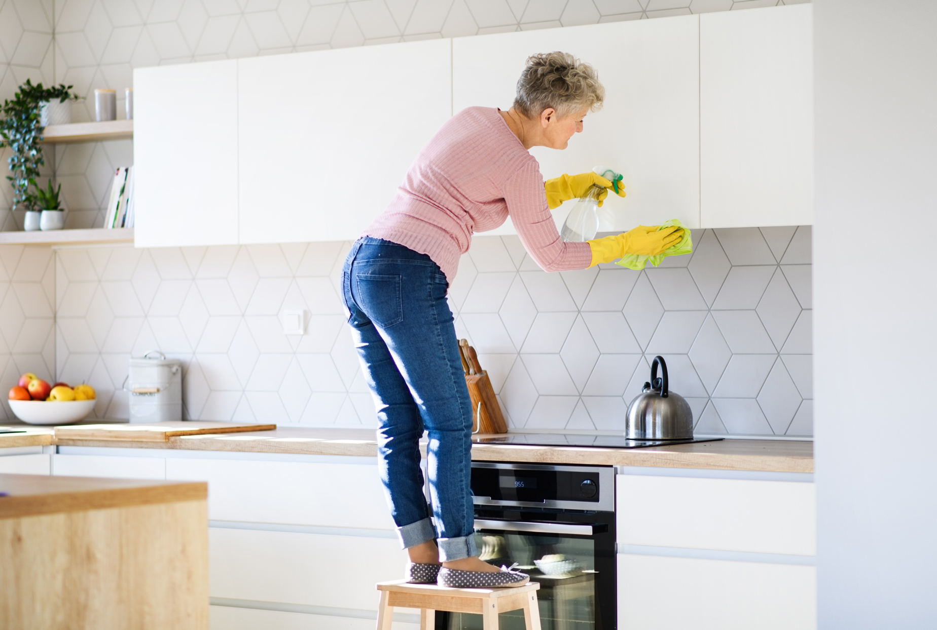 woman on step stool cleaning kitchen cabinets