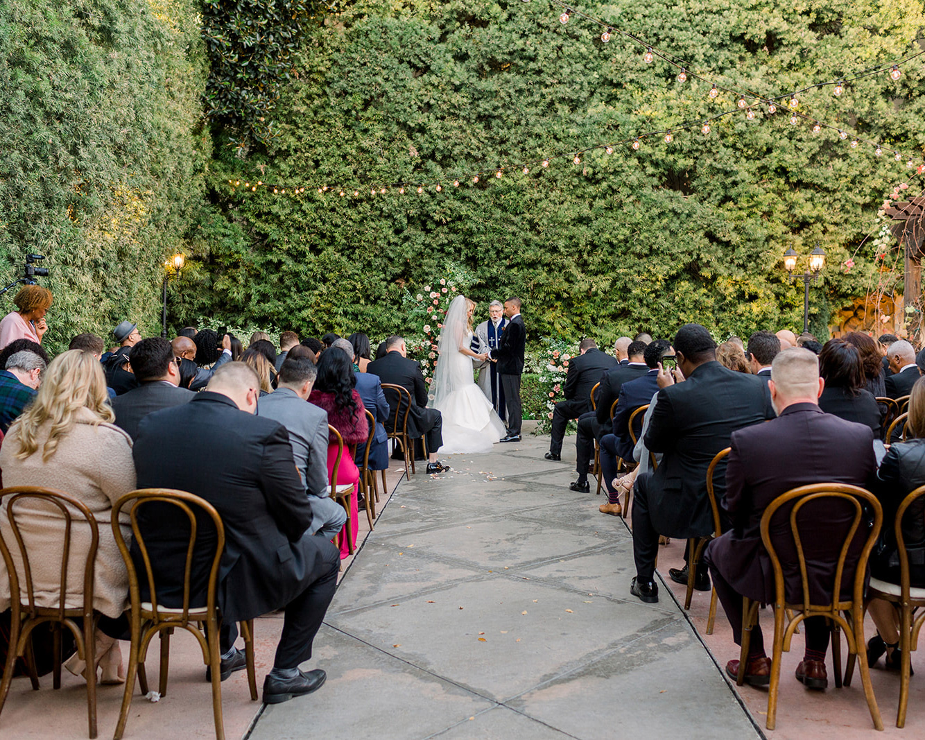 wedding ceremony outdoors with guests in wooden chairs