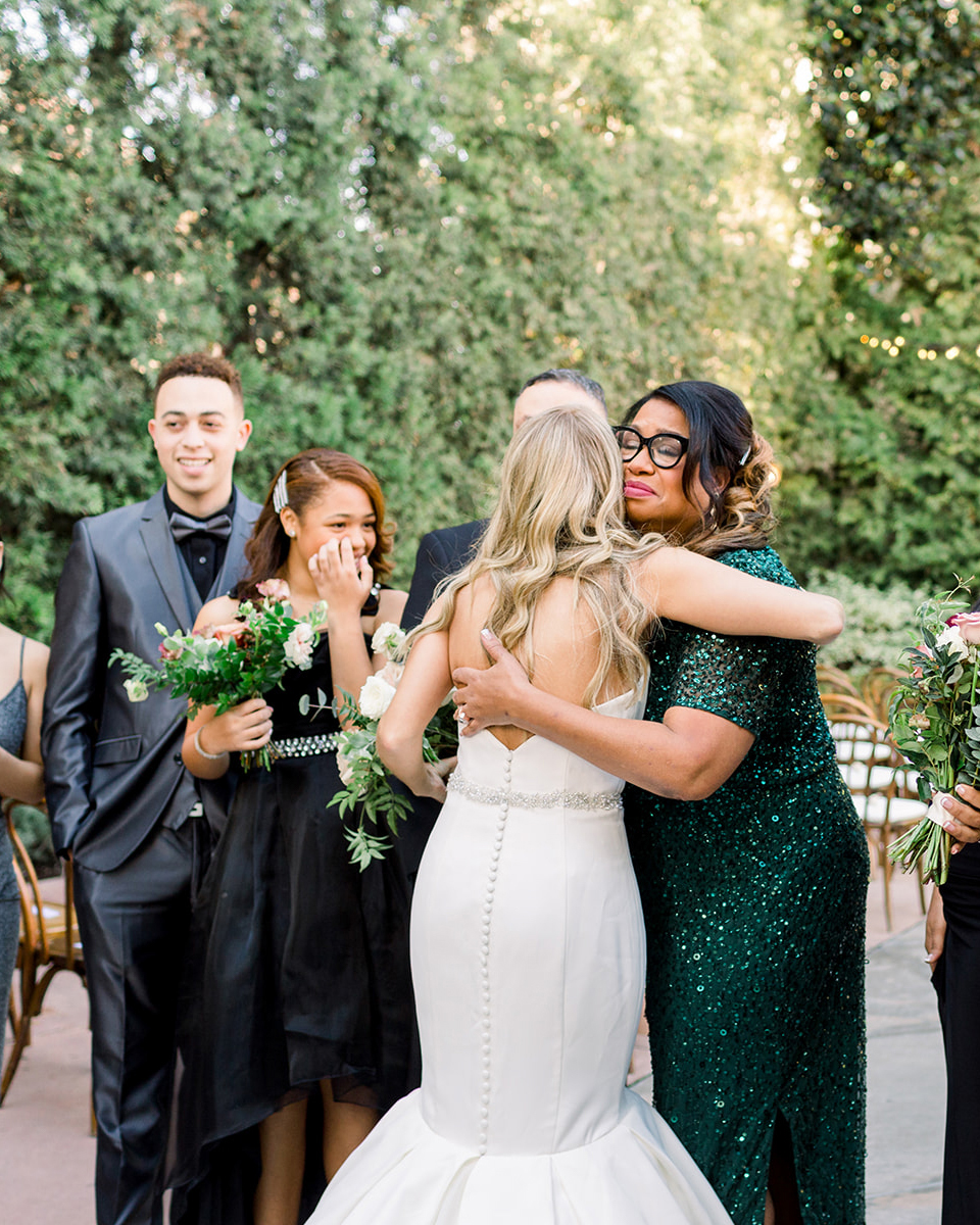 bride hugging family at wedding