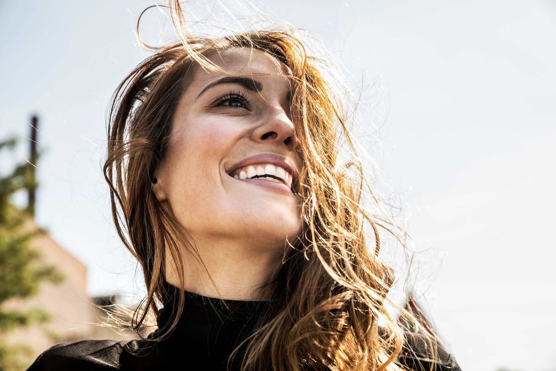 woman smiling while hair blows in wind