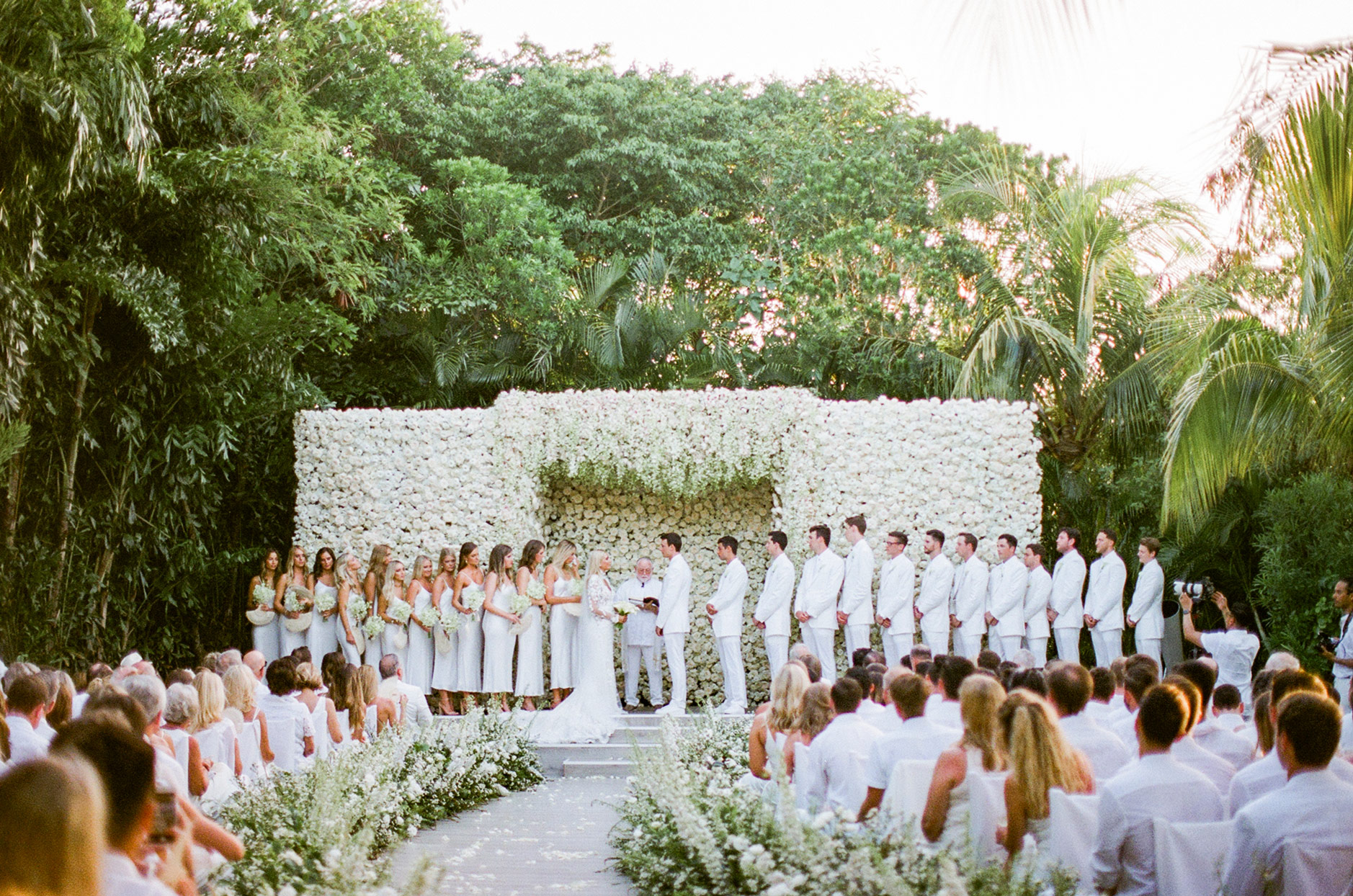 guests and bridal party wearing all white surrounded by white floral wedding displays