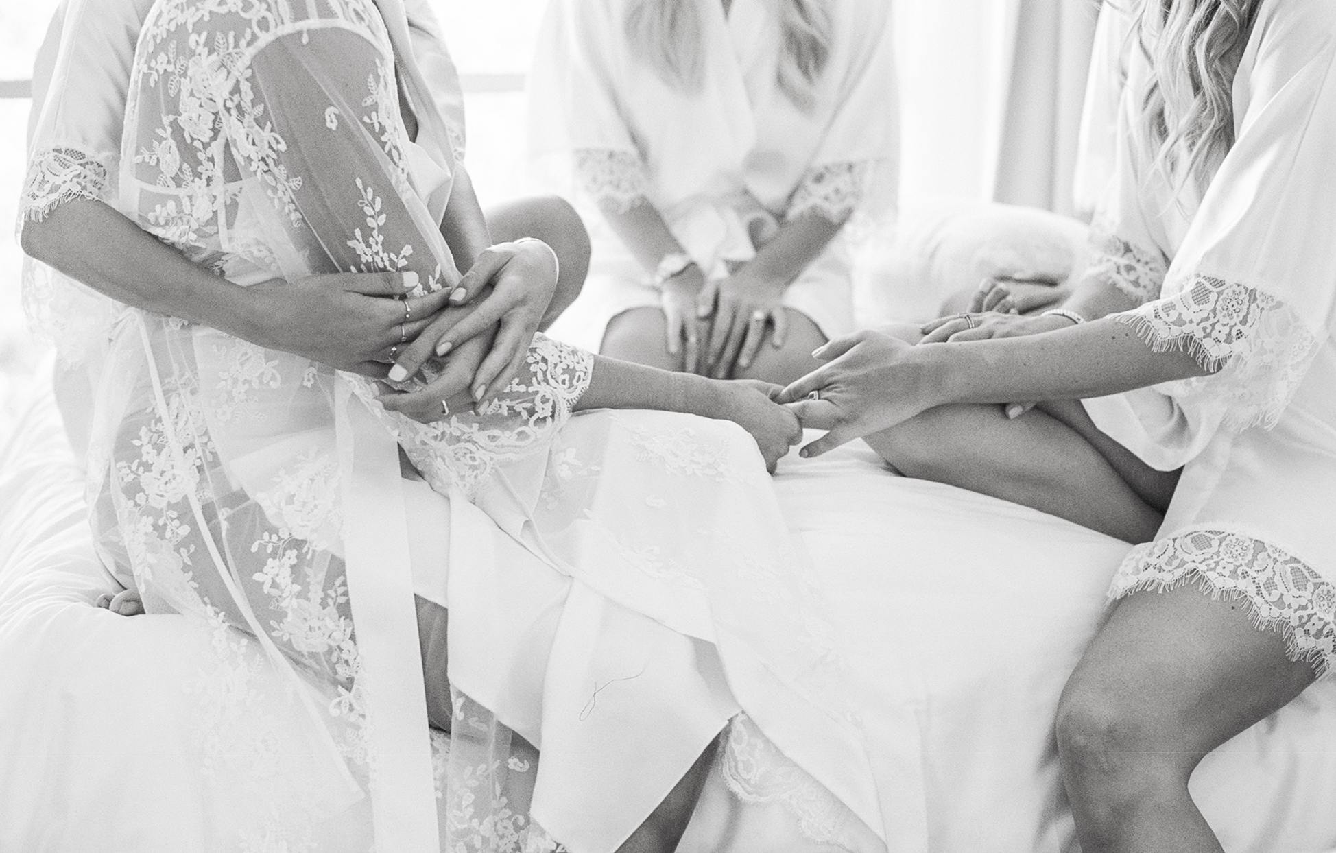 bride with bridesmaids wearing robes before wedding