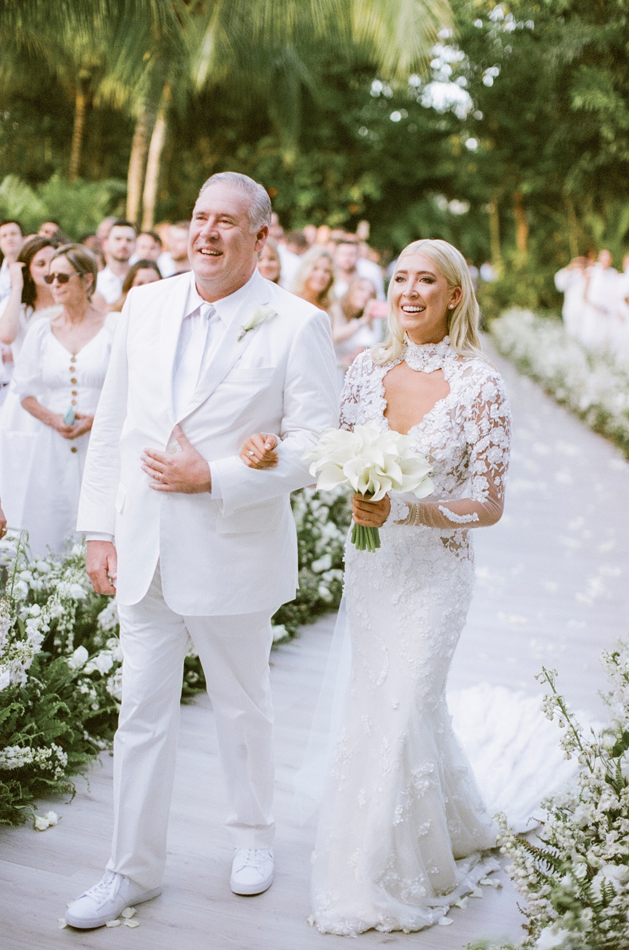 father of the bride walking bride down processional aisle smiling
