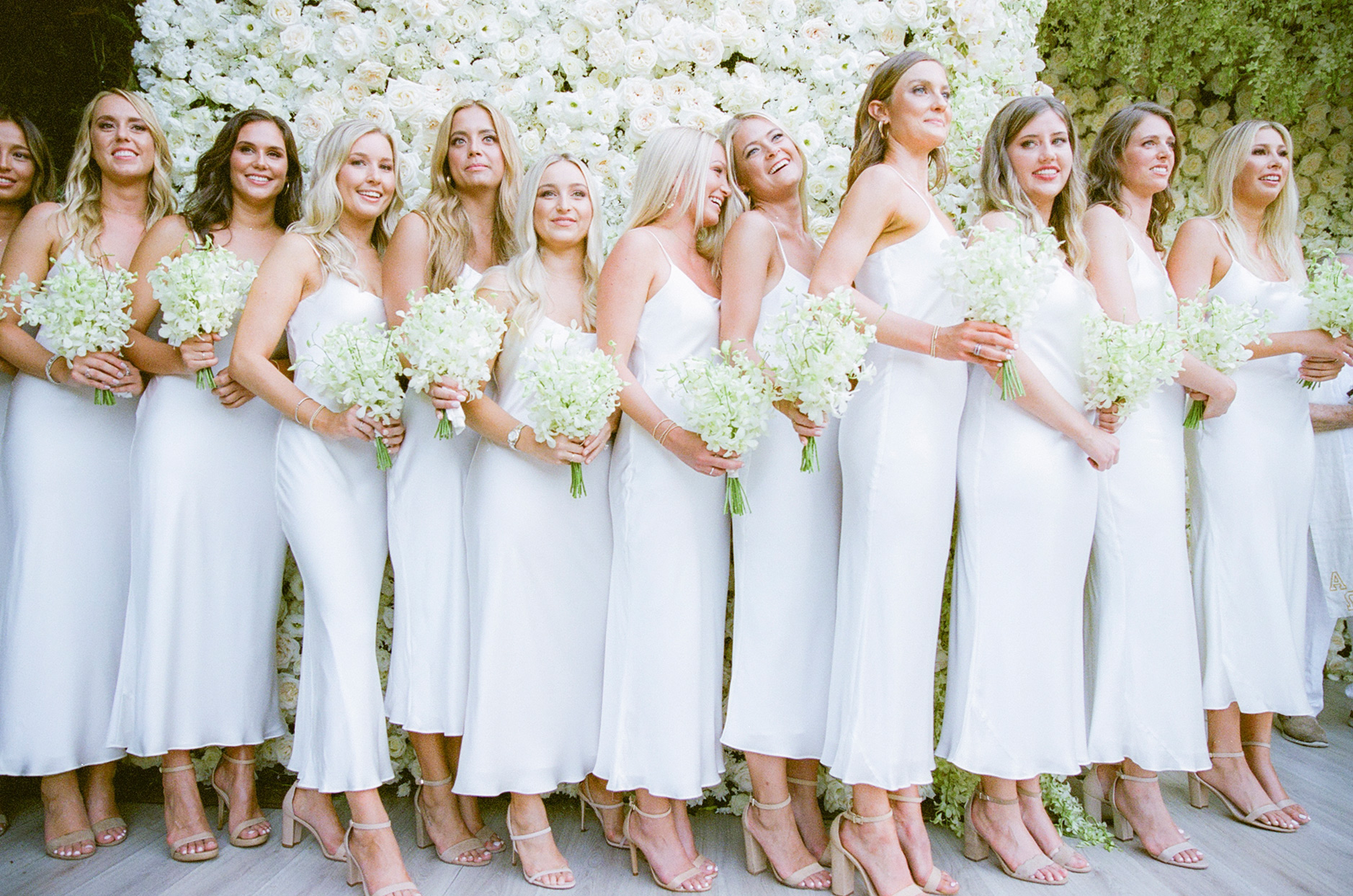 bridesmaids wearing identical ankle length white slip dresses