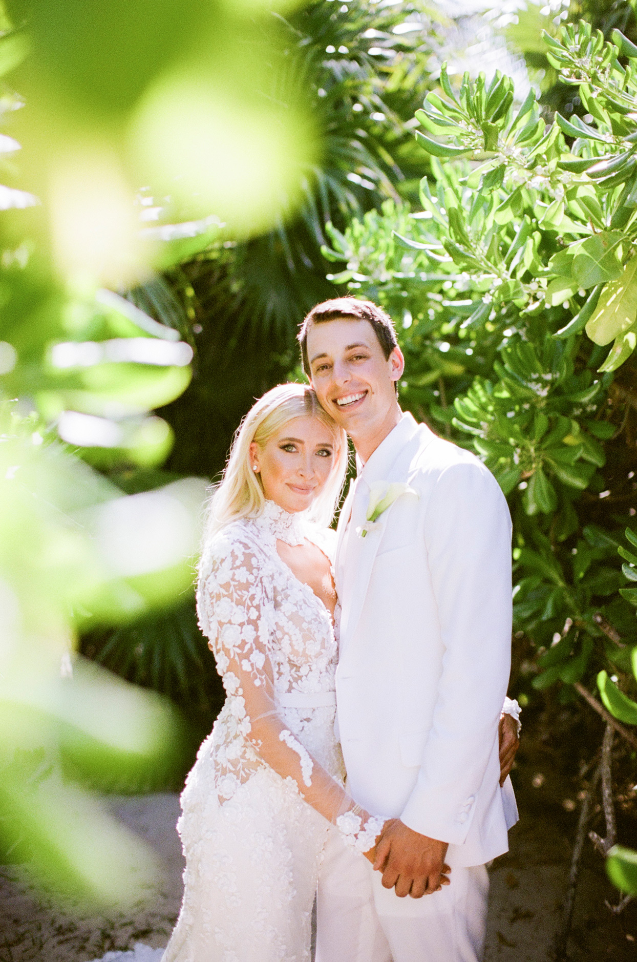 bride and groom hold hands smiling standing under greenery