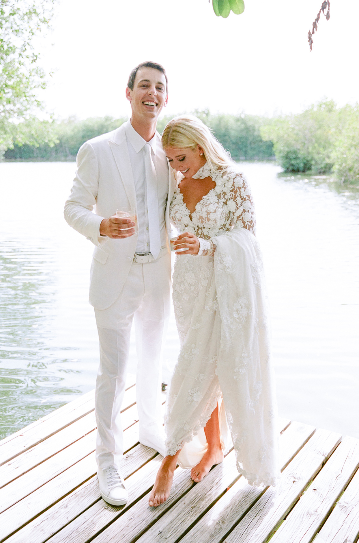 bride and groom smiling holding drinks on dock