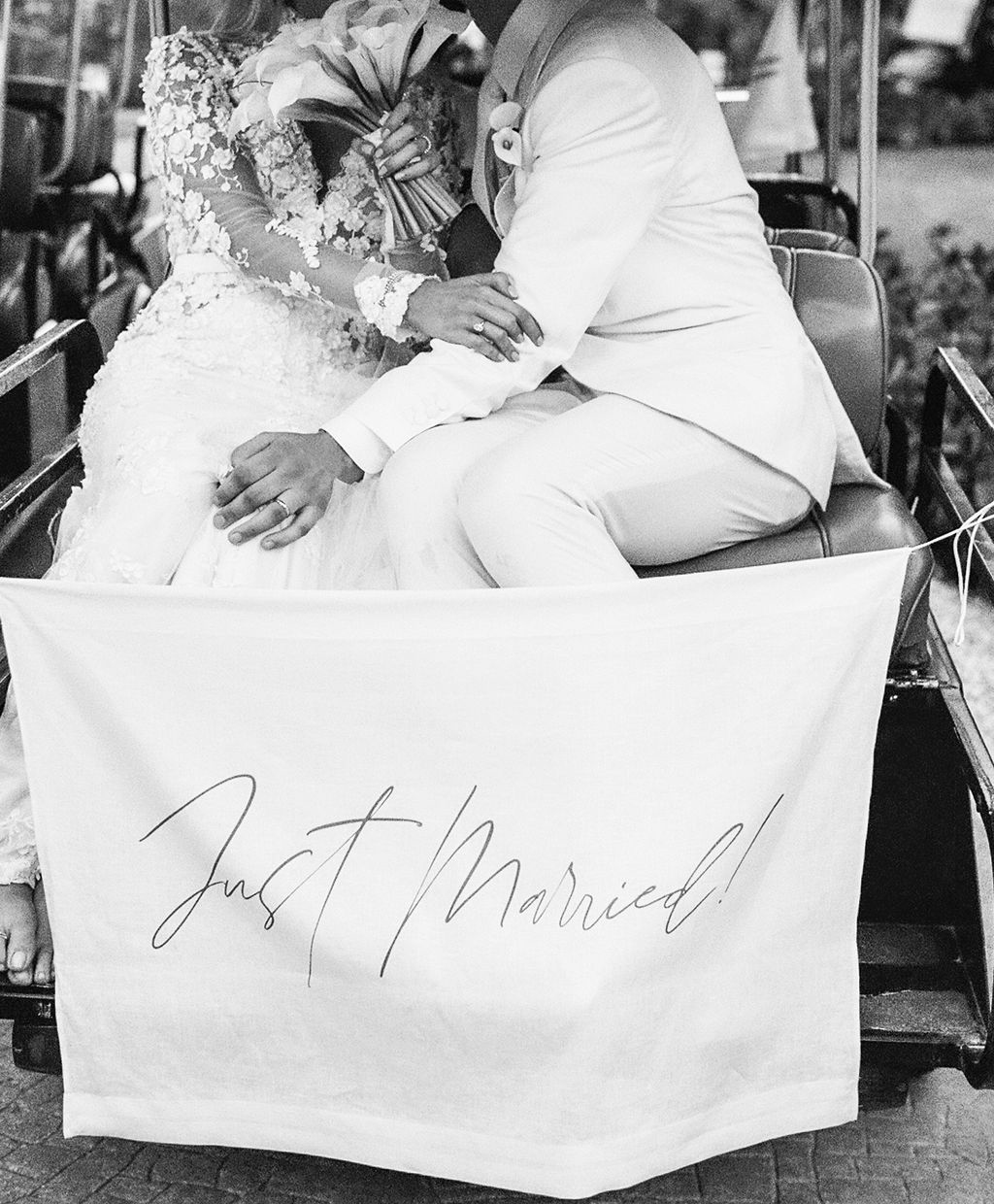 bride and groom next to just married sign