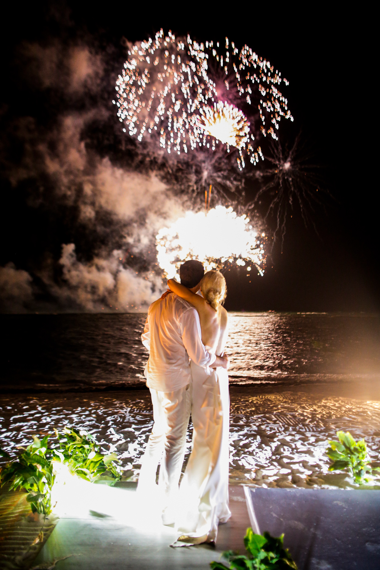bride and groom watching fireworks display on the beach