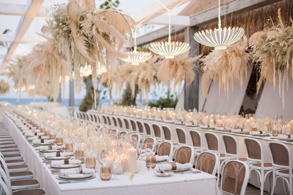 long white linen covered reception tables under hanging accent displays