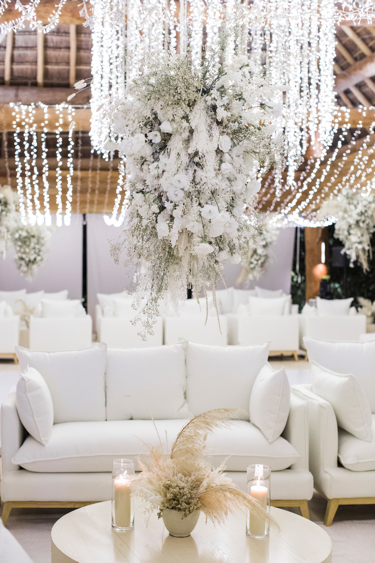 white cushioned lounge area with white floral chandeliers