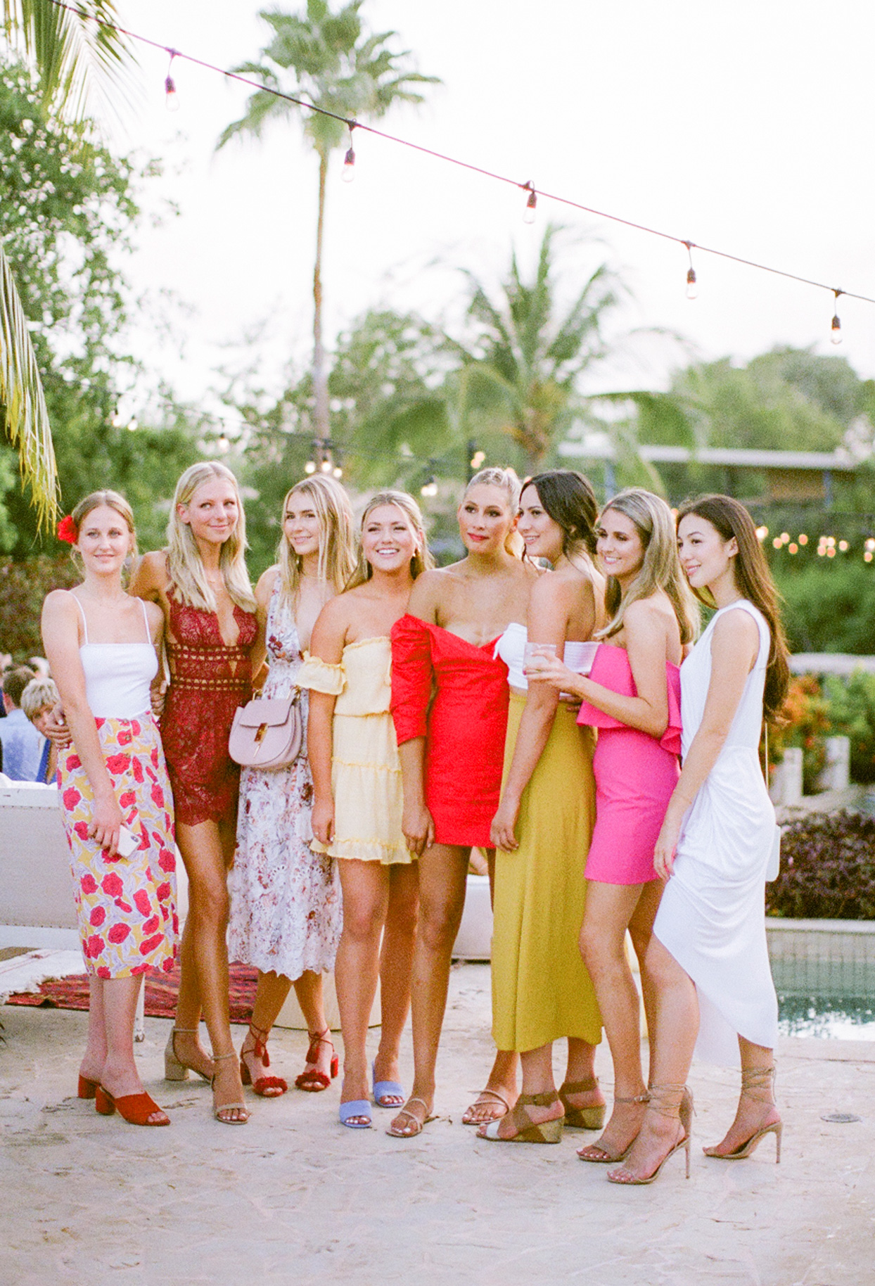 welcome party guests wearing various warm toned dresses