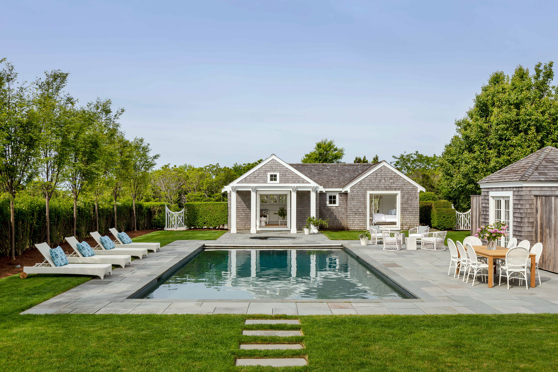 outdoor dining table and swimming pool in backyard of nantucket home