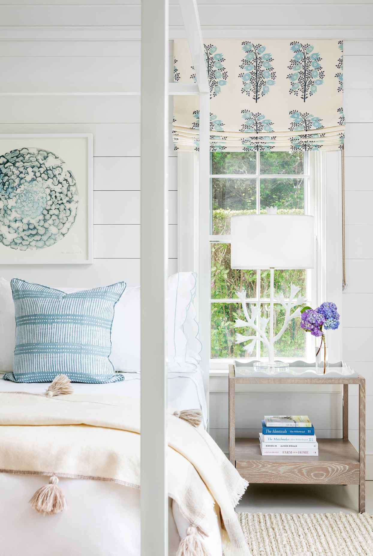 white four-poster bed with blue accent pillow