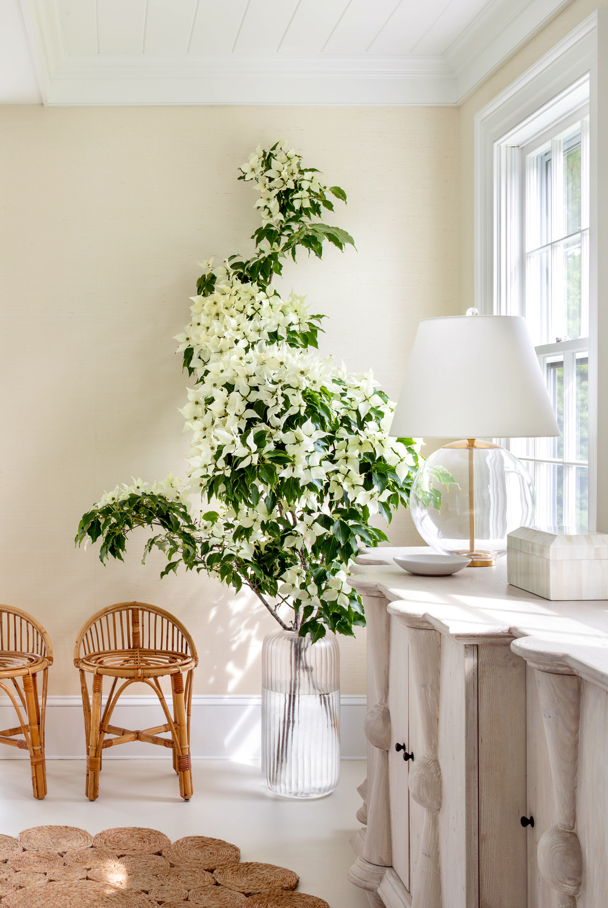 tall white flowers beside two wicker chairs
