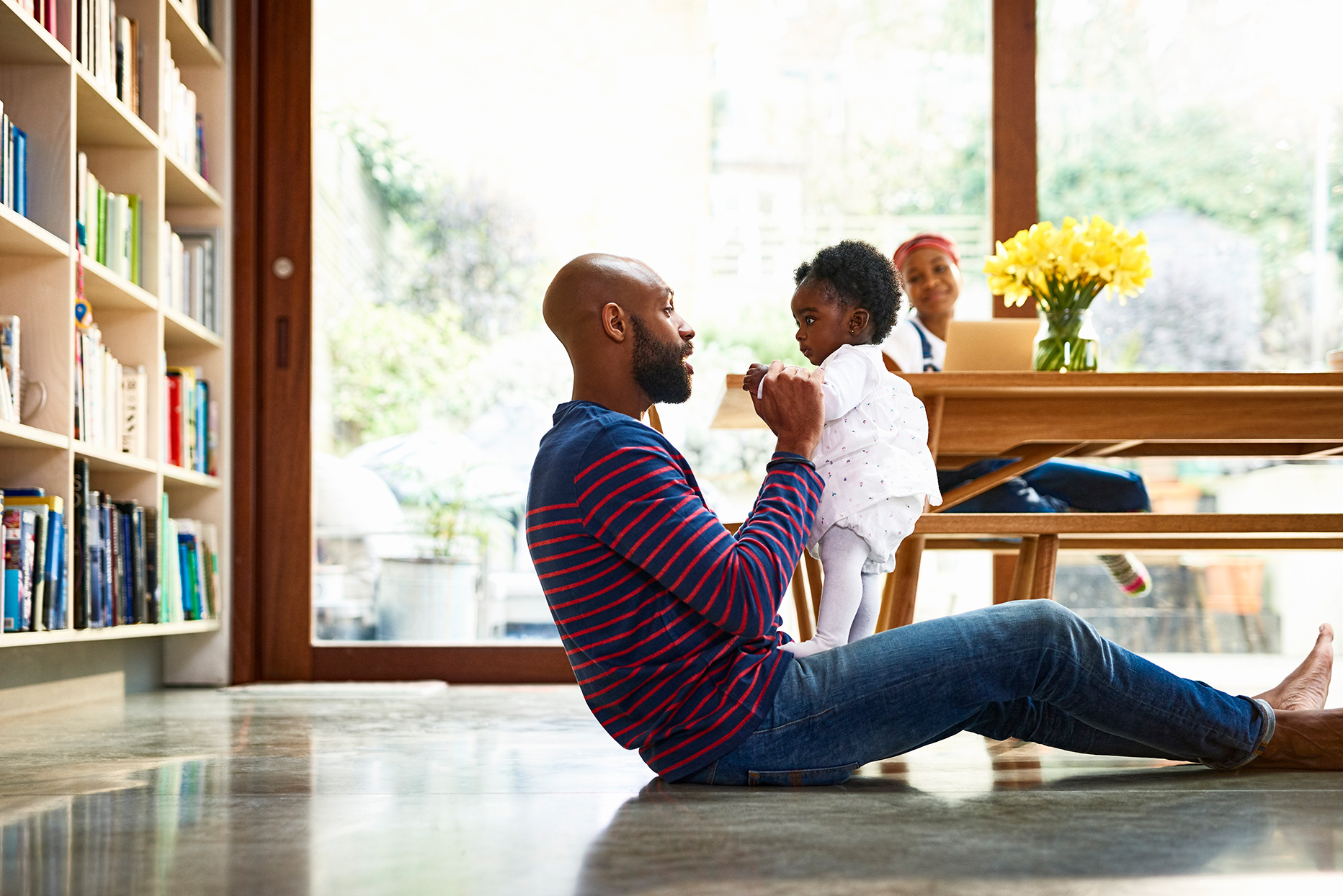 father playing with daughter on floor
