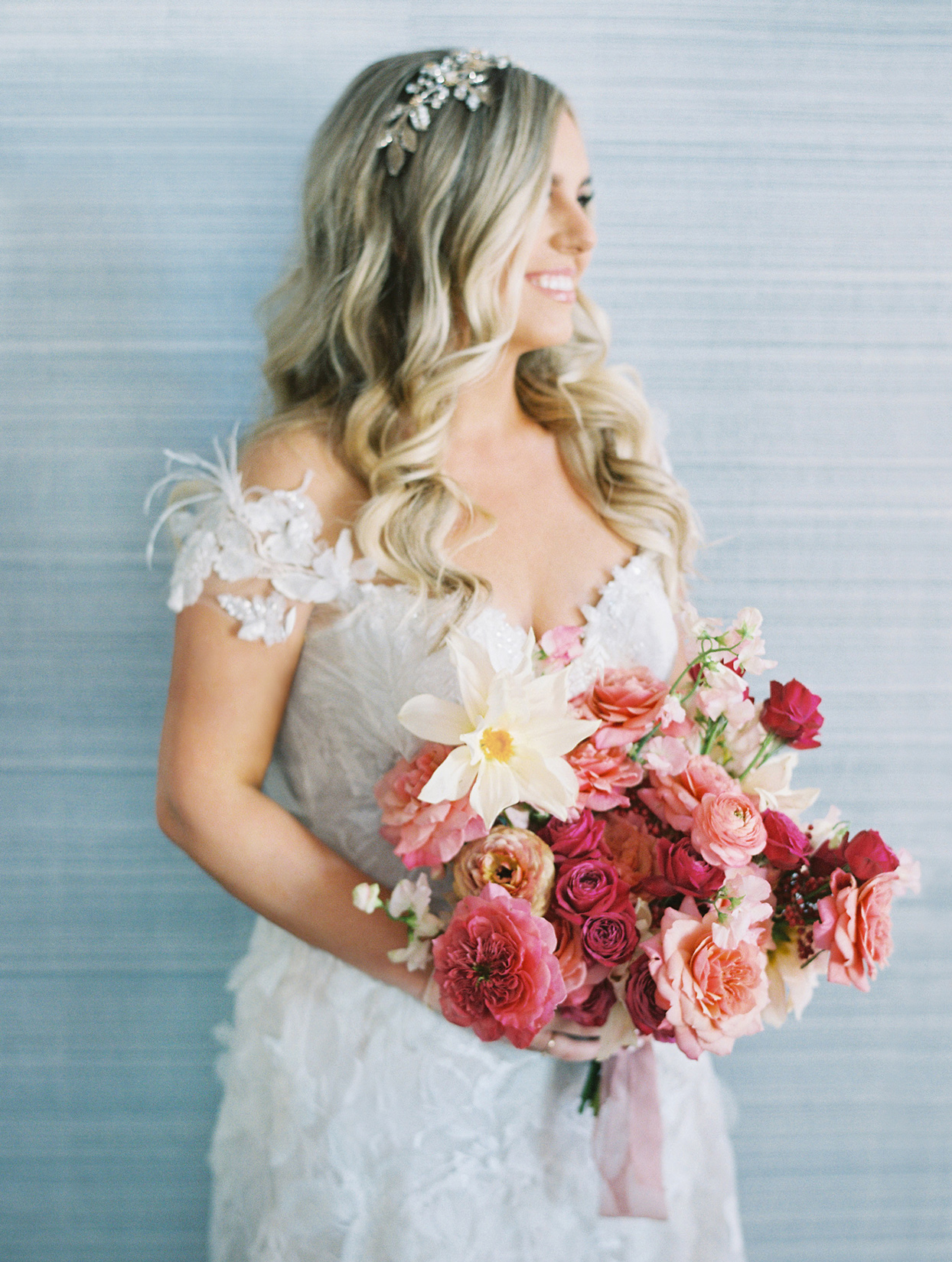 bride smiling holding red and pink floral bouquet