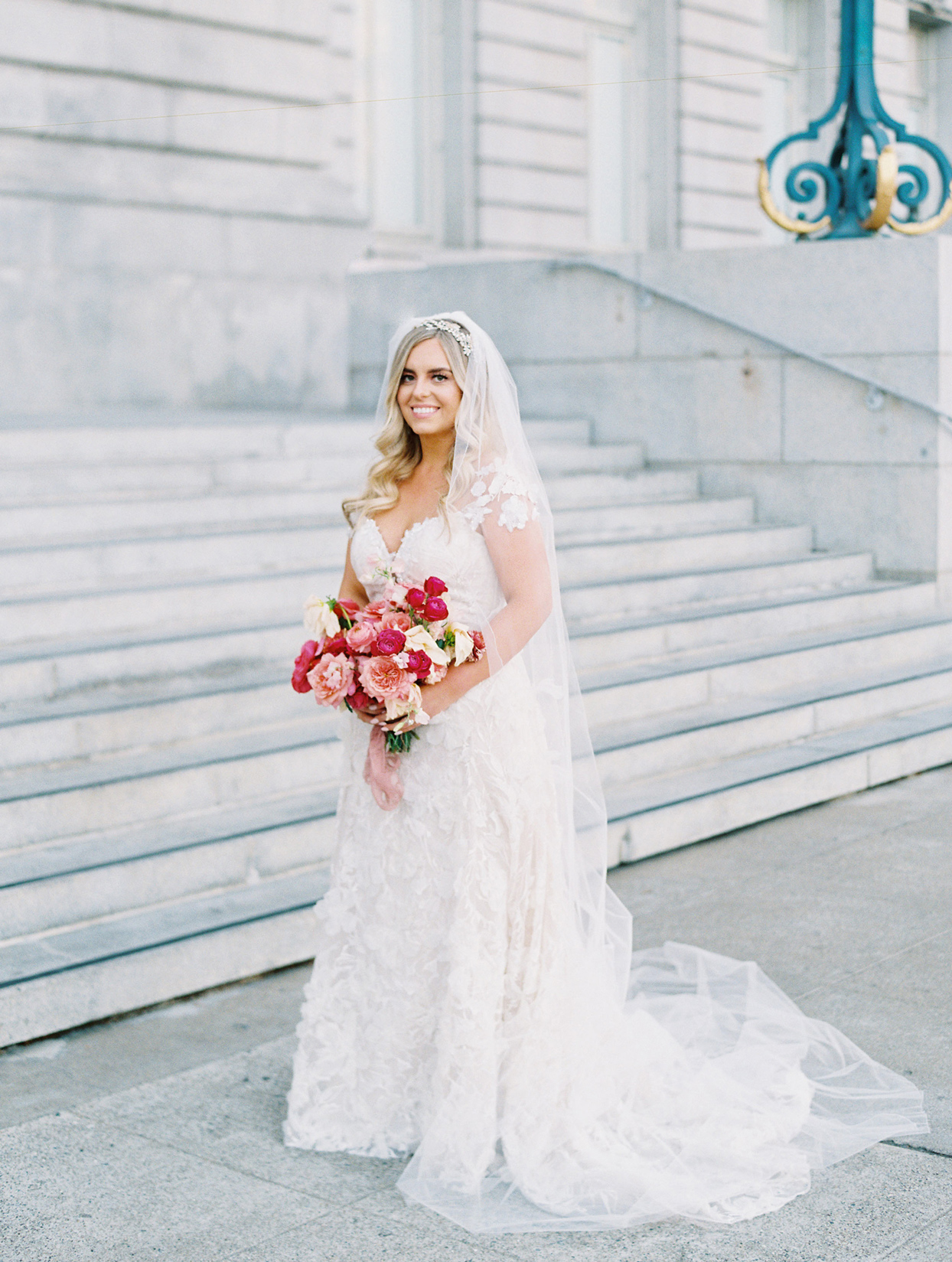 bride smiling outside venue holding red and pink floral bouquet