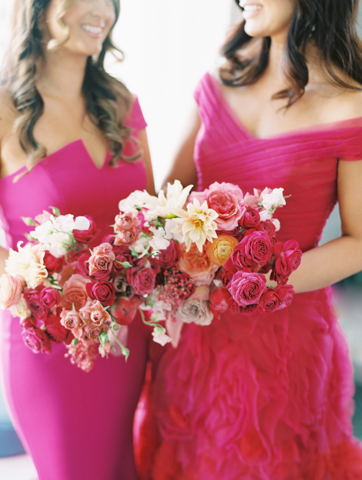 two bridesmaids holding red and pink floral bouquets with matching red and pink dresses