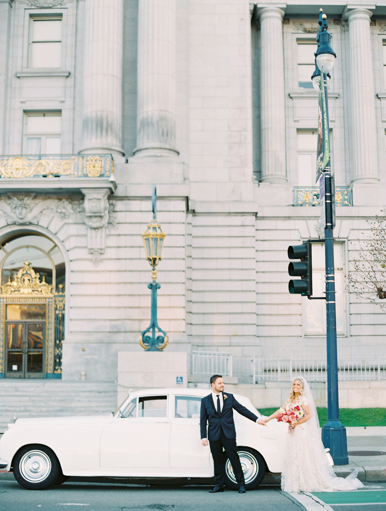 bride and groom holding hands next to white vintage car