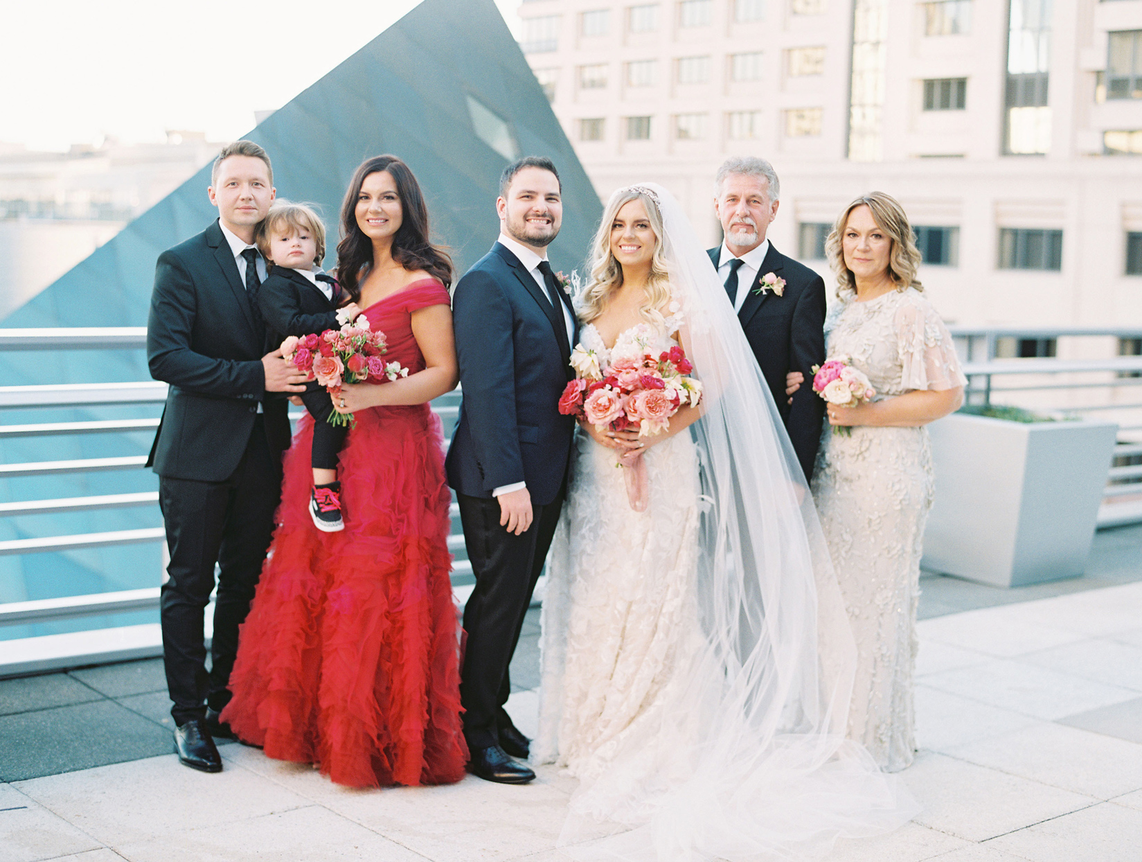 bride and groom stand outside smiling with family