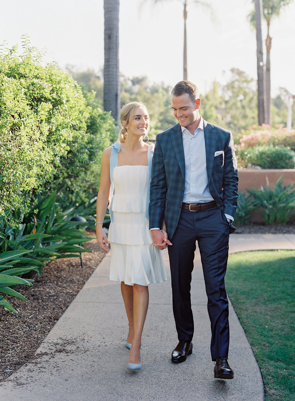couple walking down path hand in hand at rehearsal dinner
